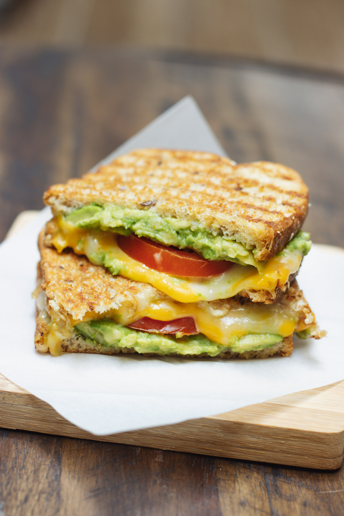 Two halves of a tomato and avocado grilled cheese sandwich stacked on parchment paper on a wooden board.