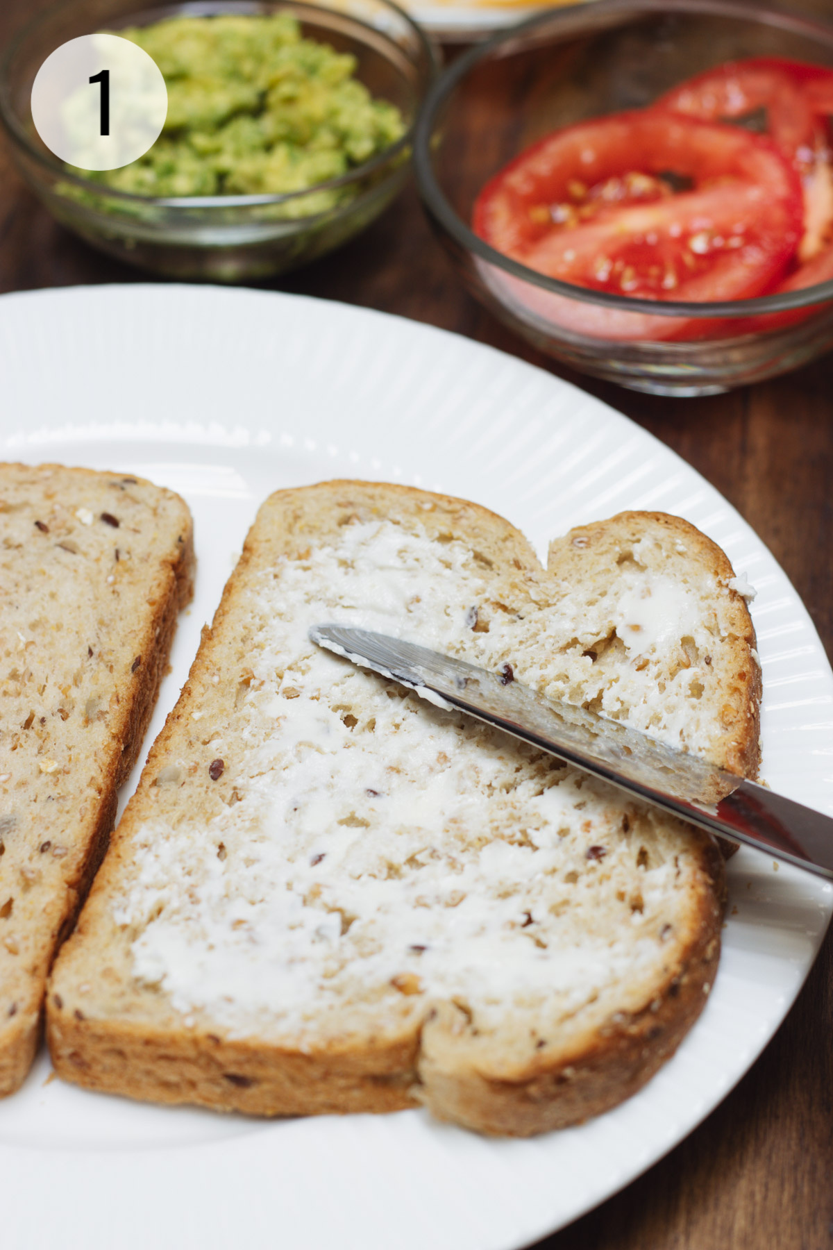 Knife spreading butter on a piece of whole grain bread with tomato and avocado in background.