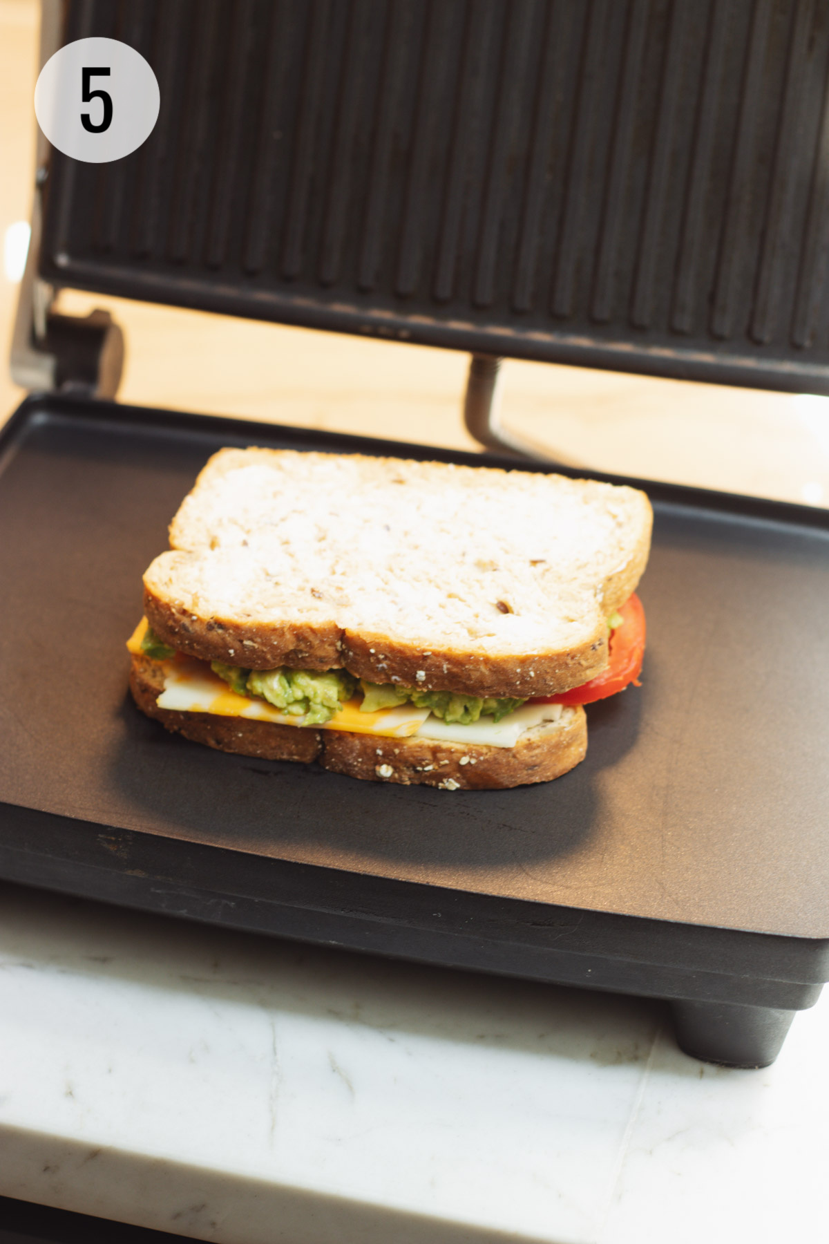 Assembled tomato and avocado grilled cheese sandwich ready to be grilled on panini maker.