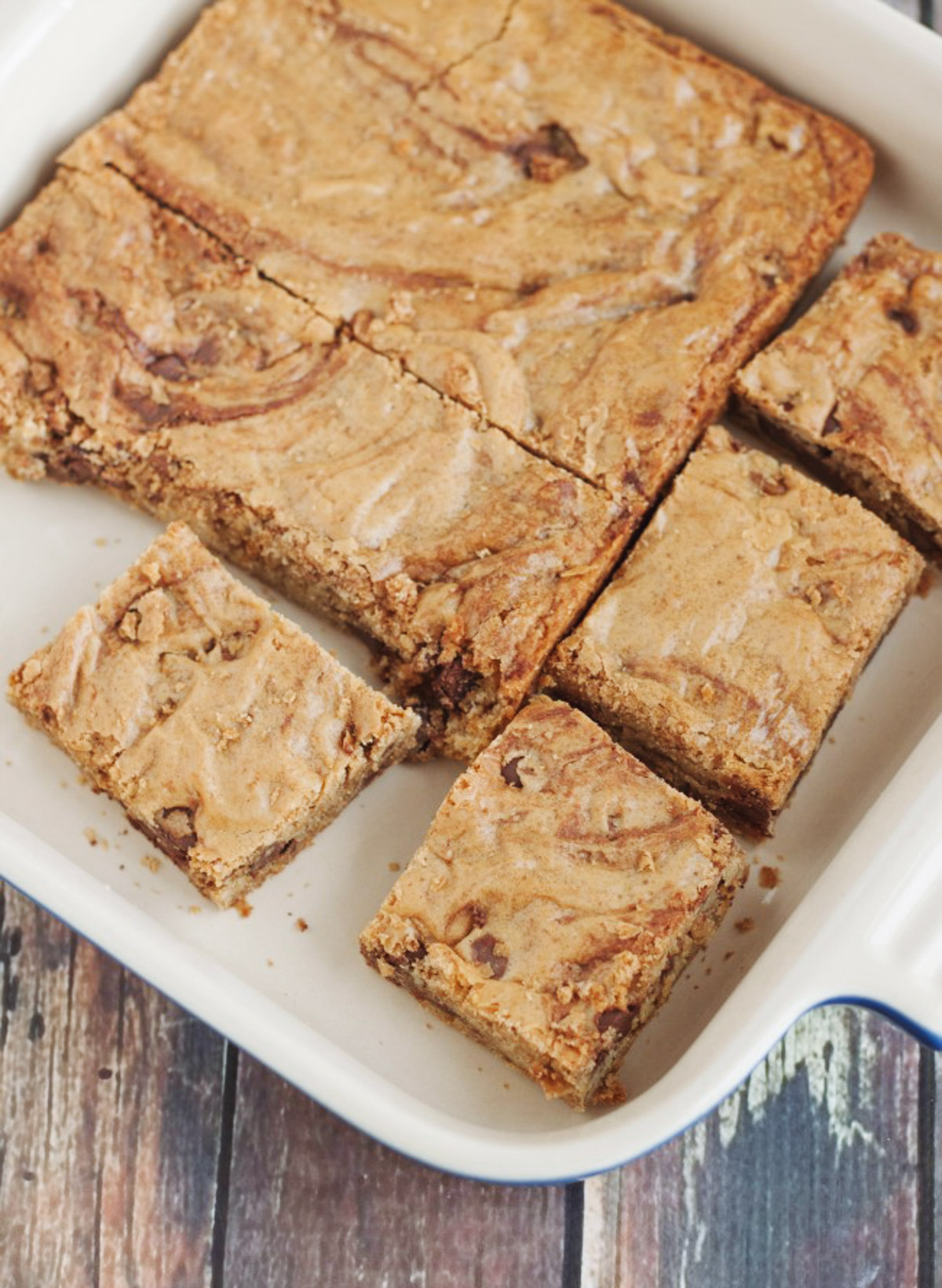 Baking pan with cut blondie bars with chocolate chips cut into squares.