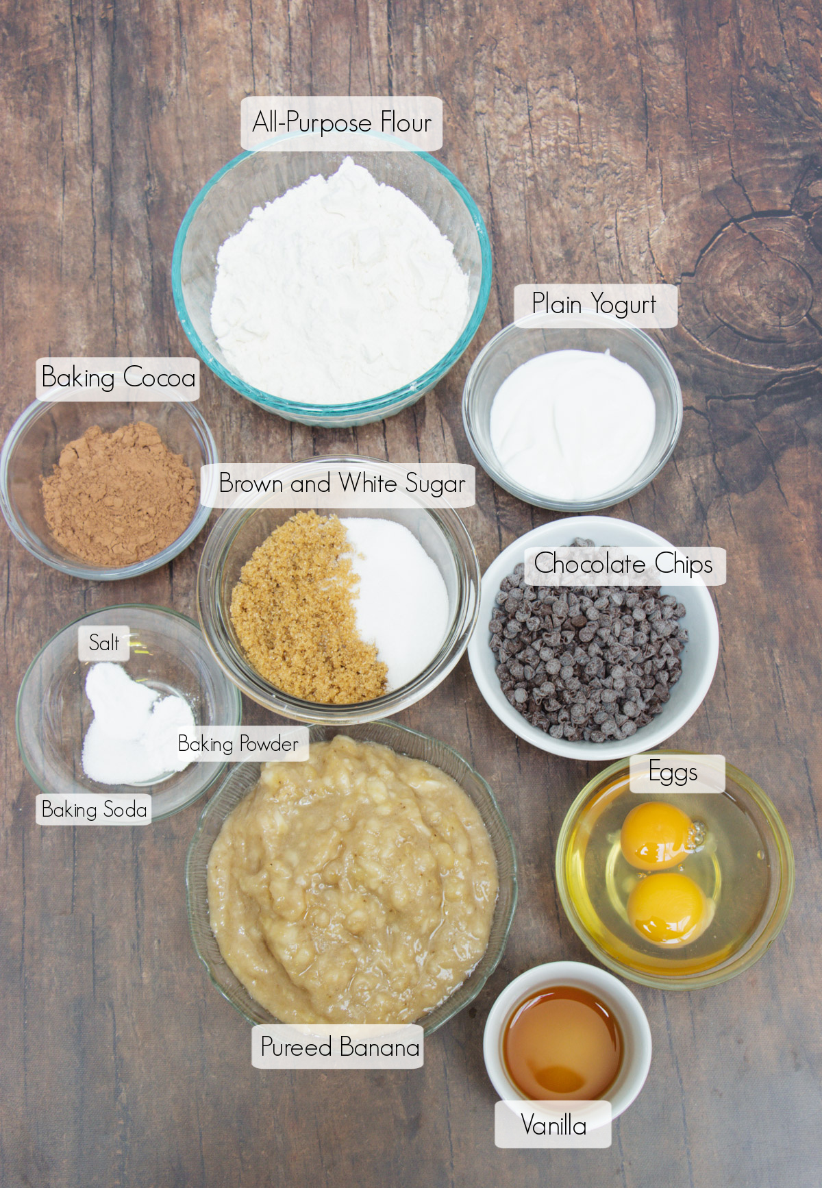 Labeled ingredients in bowls to make healthy chocolate chip banana bread.