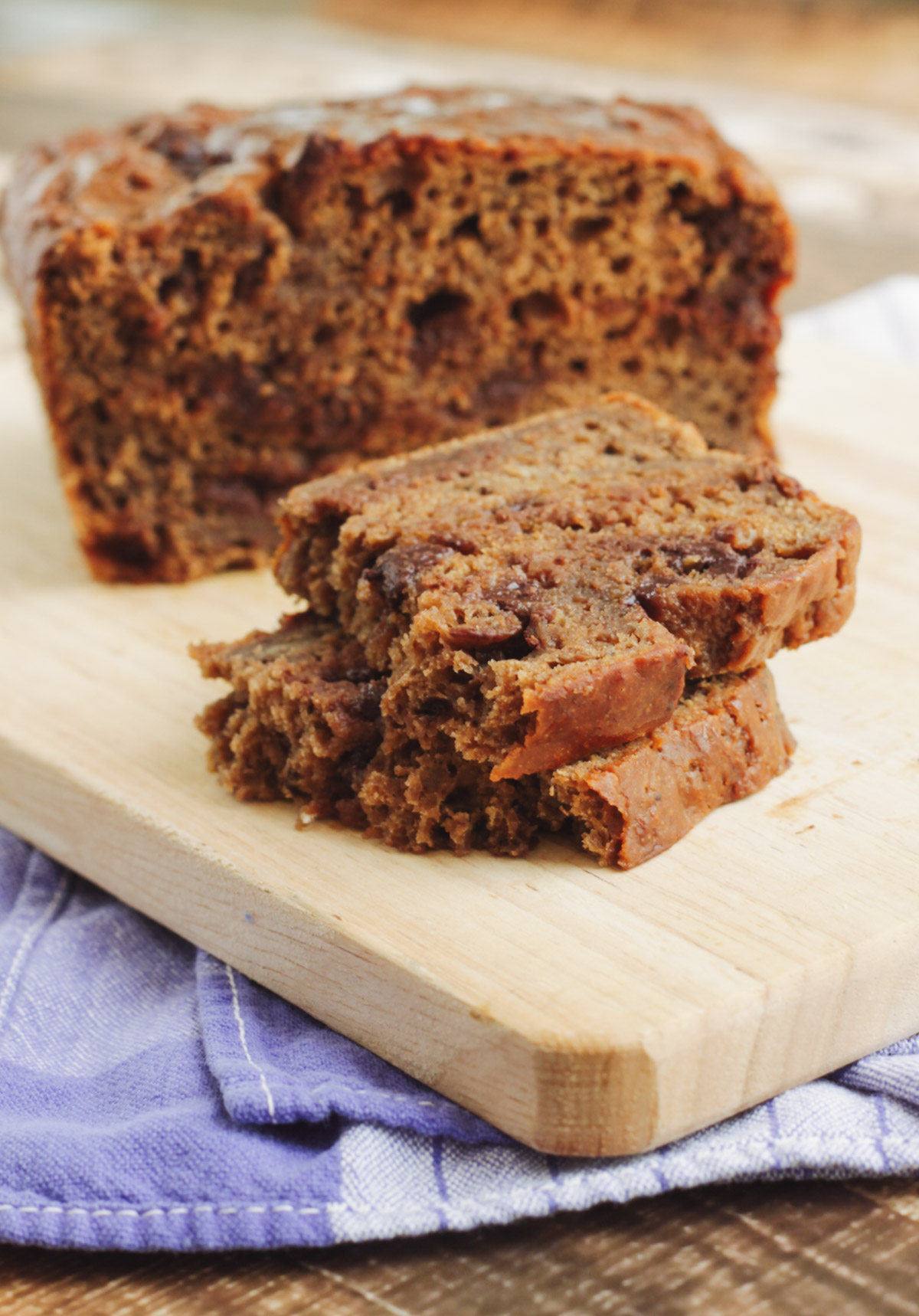 Two slices of chocolate chip banana bread with full loaf in background on a wooden cutting board and blue towel.