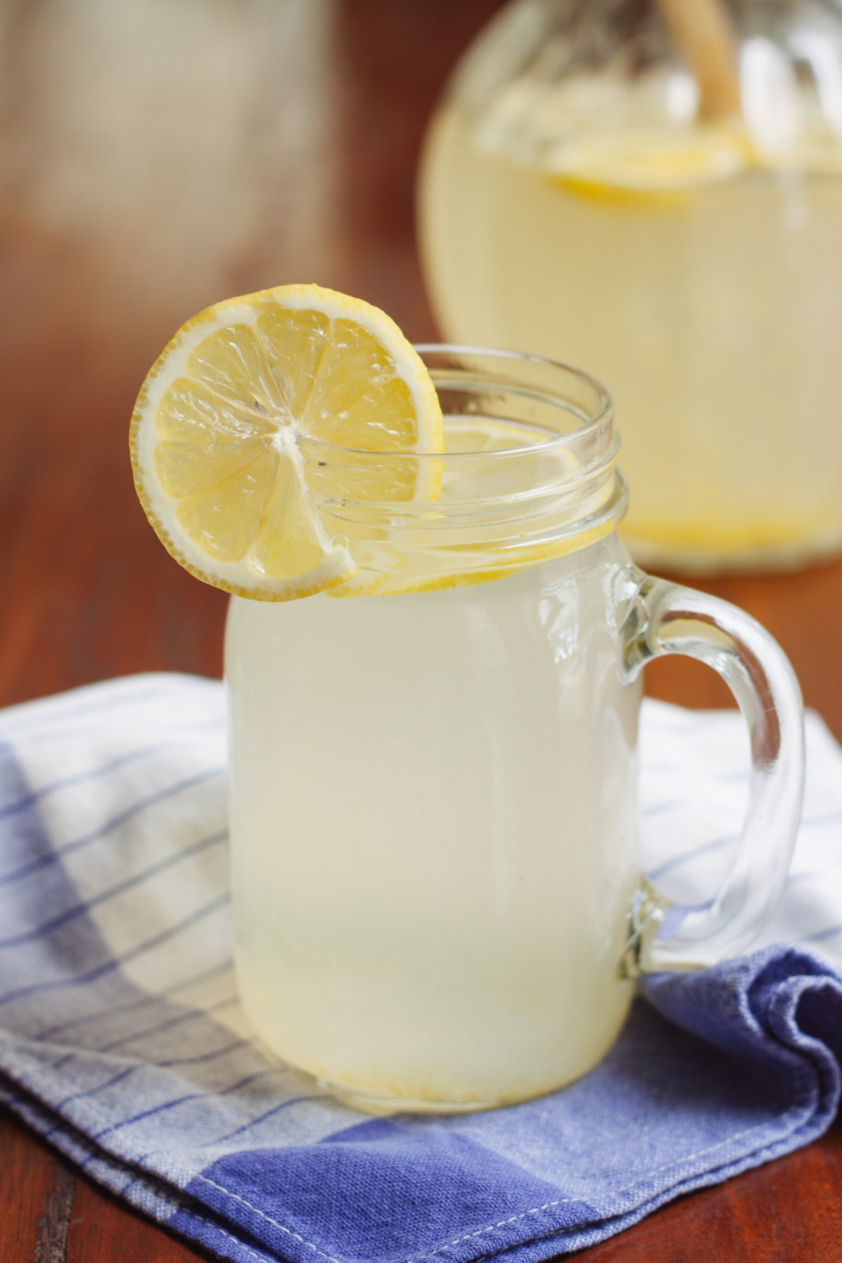 Glass mug with lemonade and lemon on top on a blue and white towel with pitcher of lemonade in background.