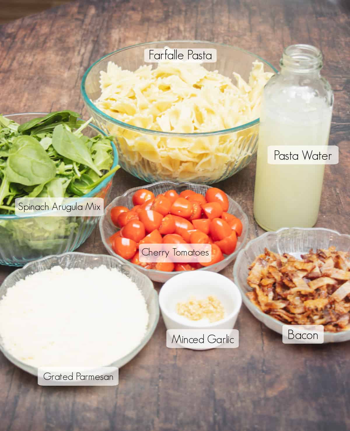 Labeled ingredients in bowls and jar to make Bacon Spinach and Tomato Pasta.