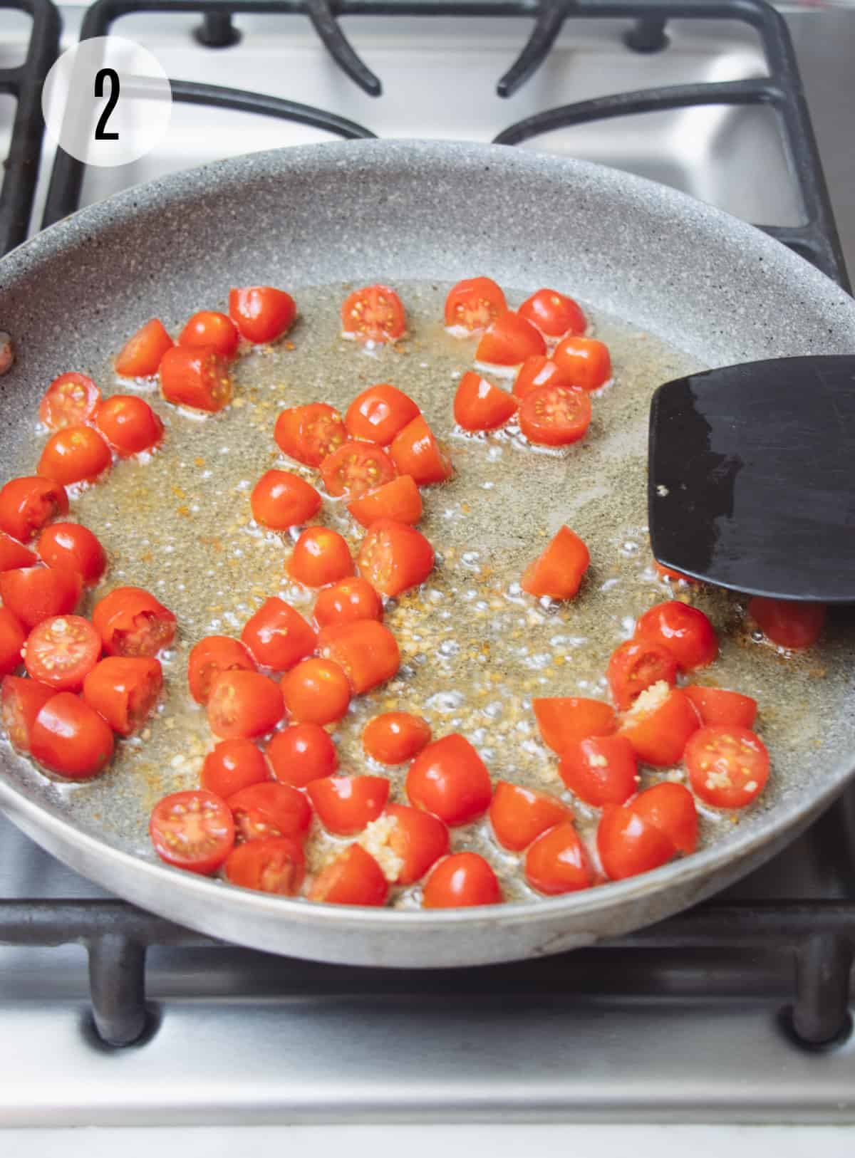 Sliced grape tomatoes sauteing in bacon fat in a grey skillet with black spatula.