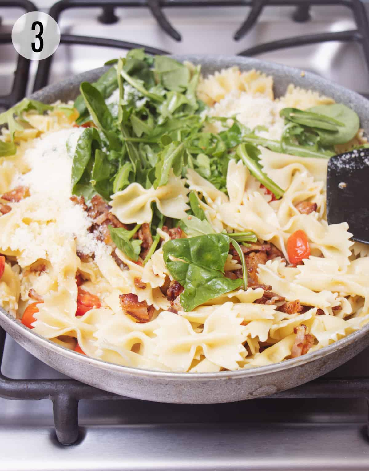 Skillet with baby spinach leaves, bow-tie pasta, chopped bacon and tomatoes.