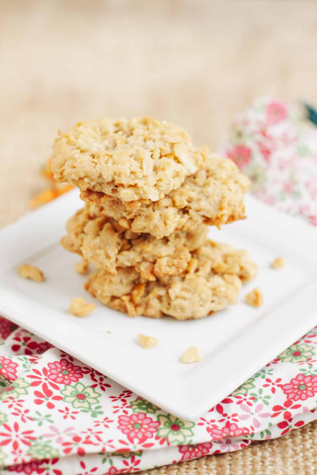 Stack of Cracker Jack Rice Crispie Cookies on a square white plate on a pink, green and white napkin.