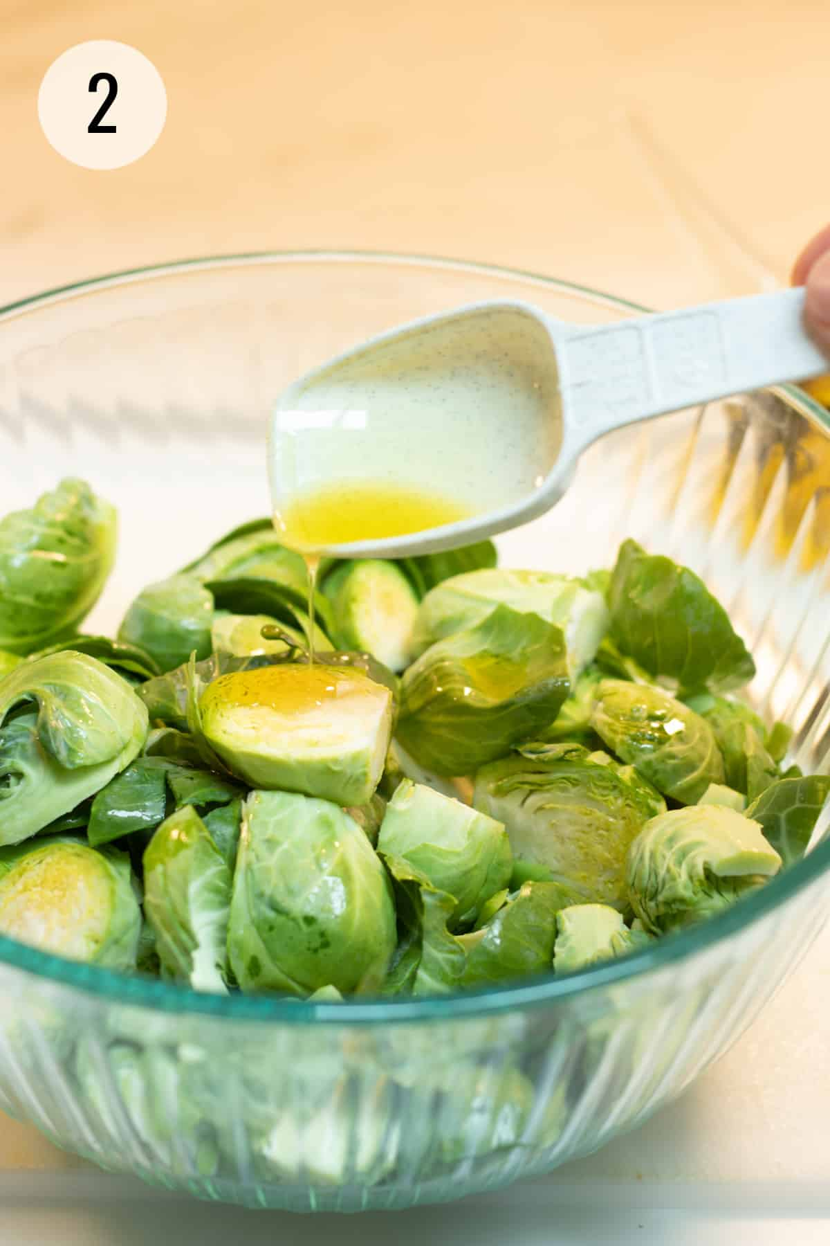 White measuring spoon drizzling olive oil in glass bowl full of cut Brussels sprouts.