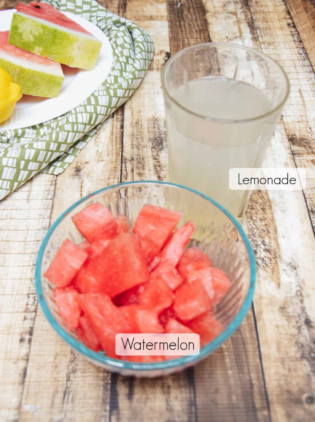 Glass bowl with cubed watermelon and glass of lemonade, both labeled, with plate of watermelon slices and lemon in upper left corner.