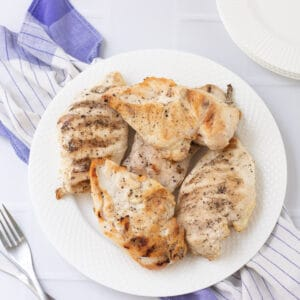 White plate with grilled chicken breasts on a blue and white towel with silver fork to side.