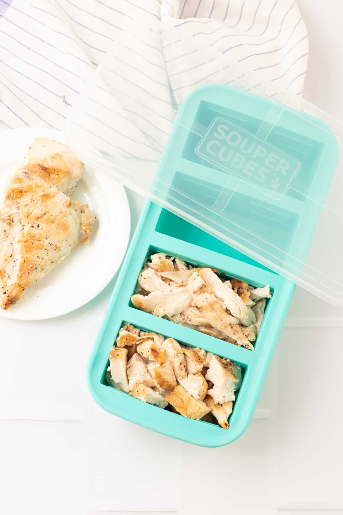 Aqua SouperCubes freezer tray with cubed and shredded chicken and clear lid on upper tray and single chicken breast on plate to left.