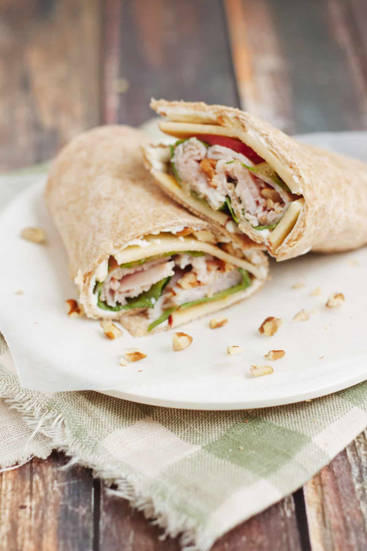 Deli turkey, lettuce and sliced apples wrapped in whole wheat tortilla with pecans scattered on plate on top of green and white check fabric.
