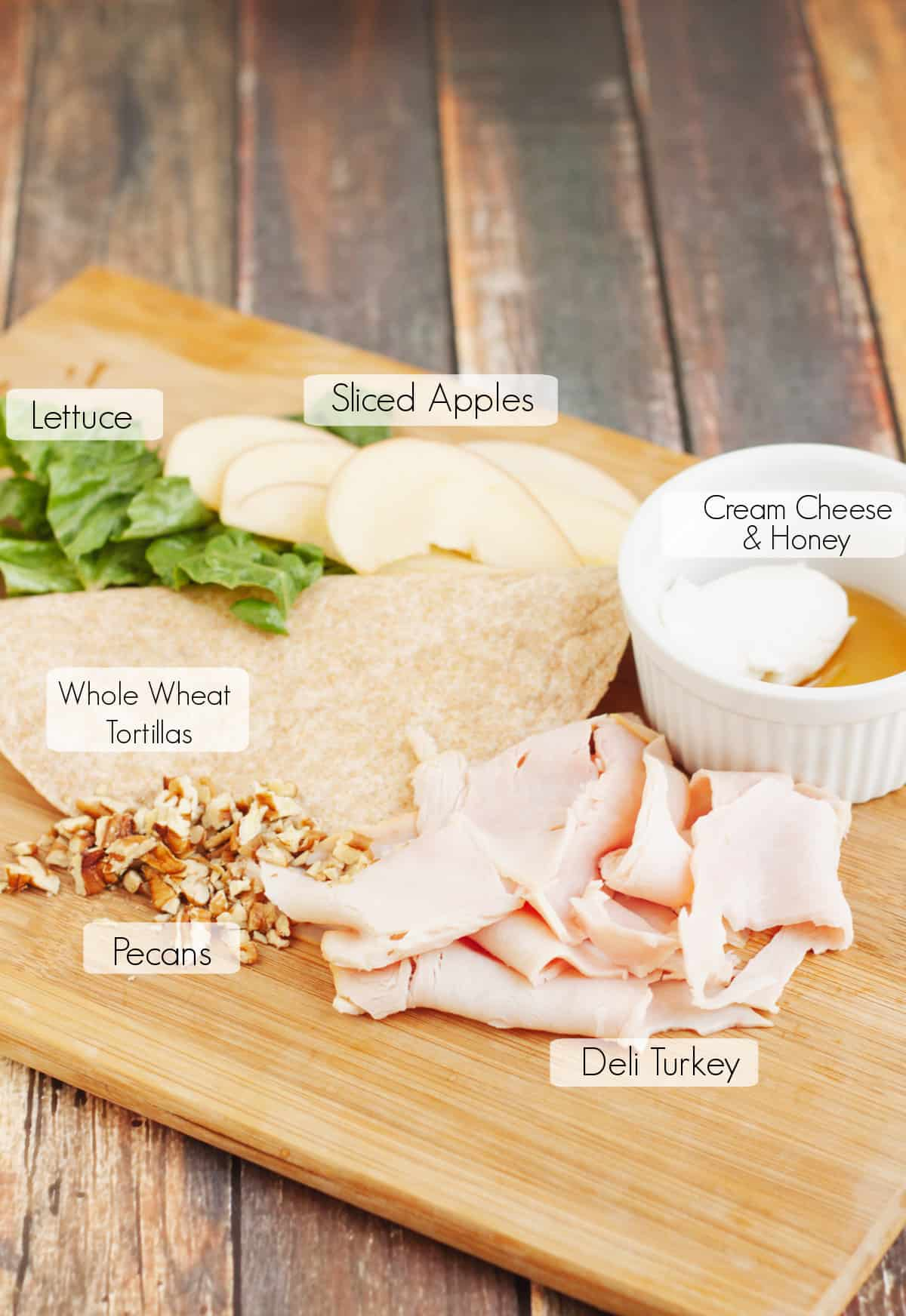 Labeled ingredients on wooden cutting board to make a turkey wrap sandwich.