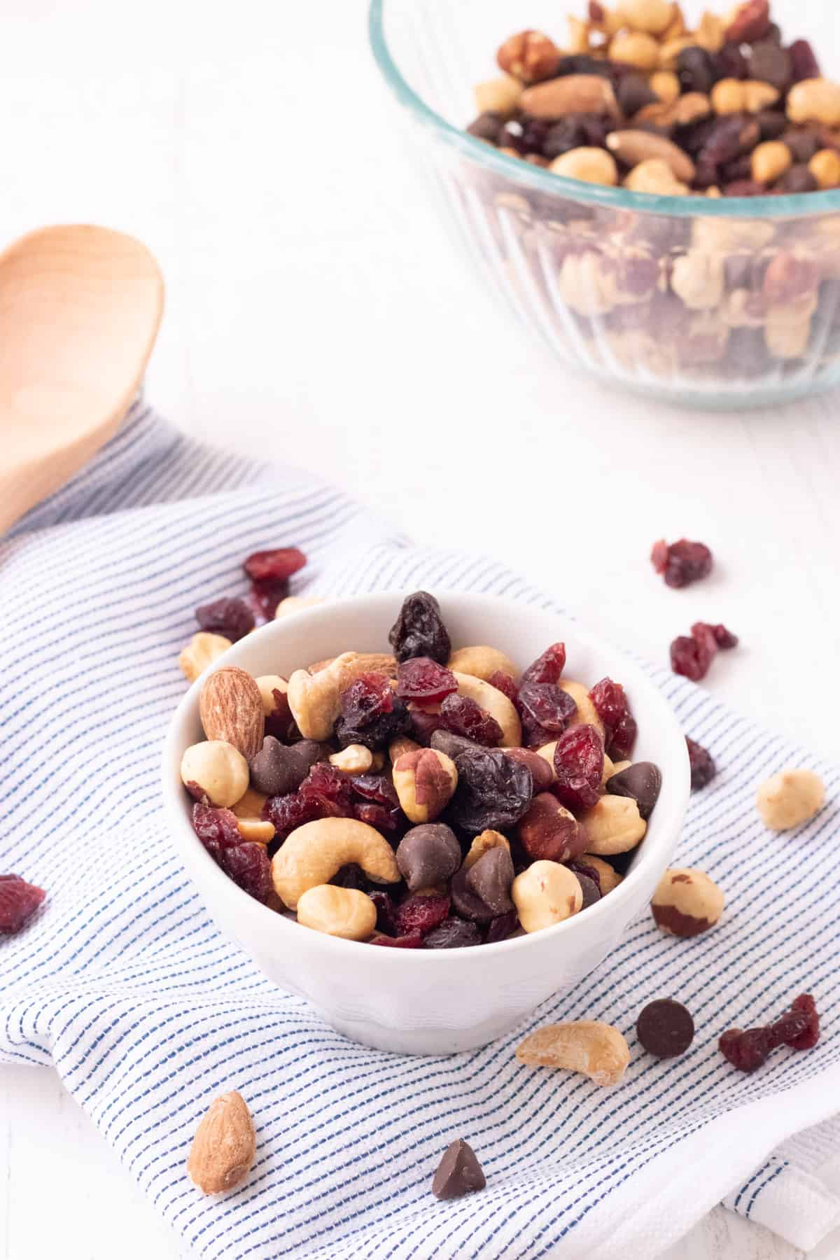 Small white bowl with roasted nuts and dried cherries and cranberries and sprinkled on a blue and white striped towel with wooden spoon and bowl of trail mix in upper background.
