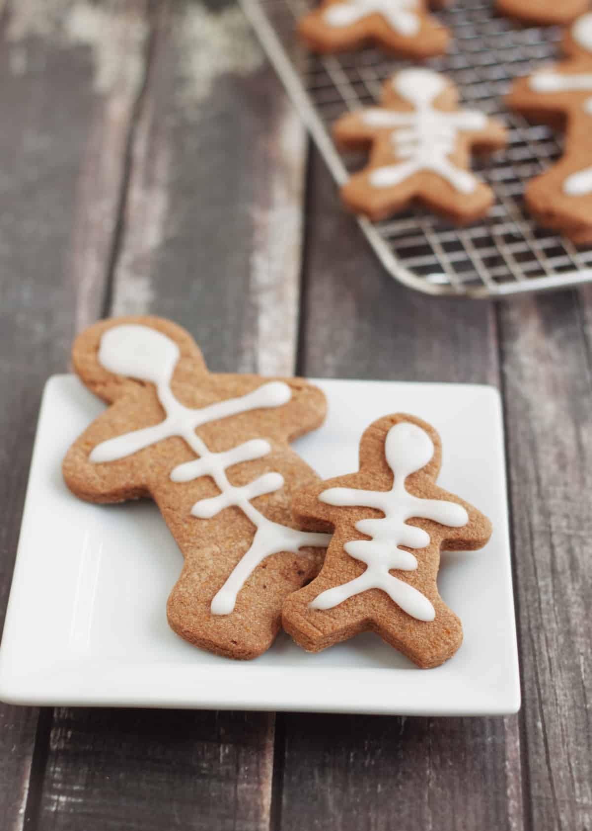 Mexican chocolate sugar cookies decorated to look like skeletons placed on a white plate with extras on a baking rack in upper right.