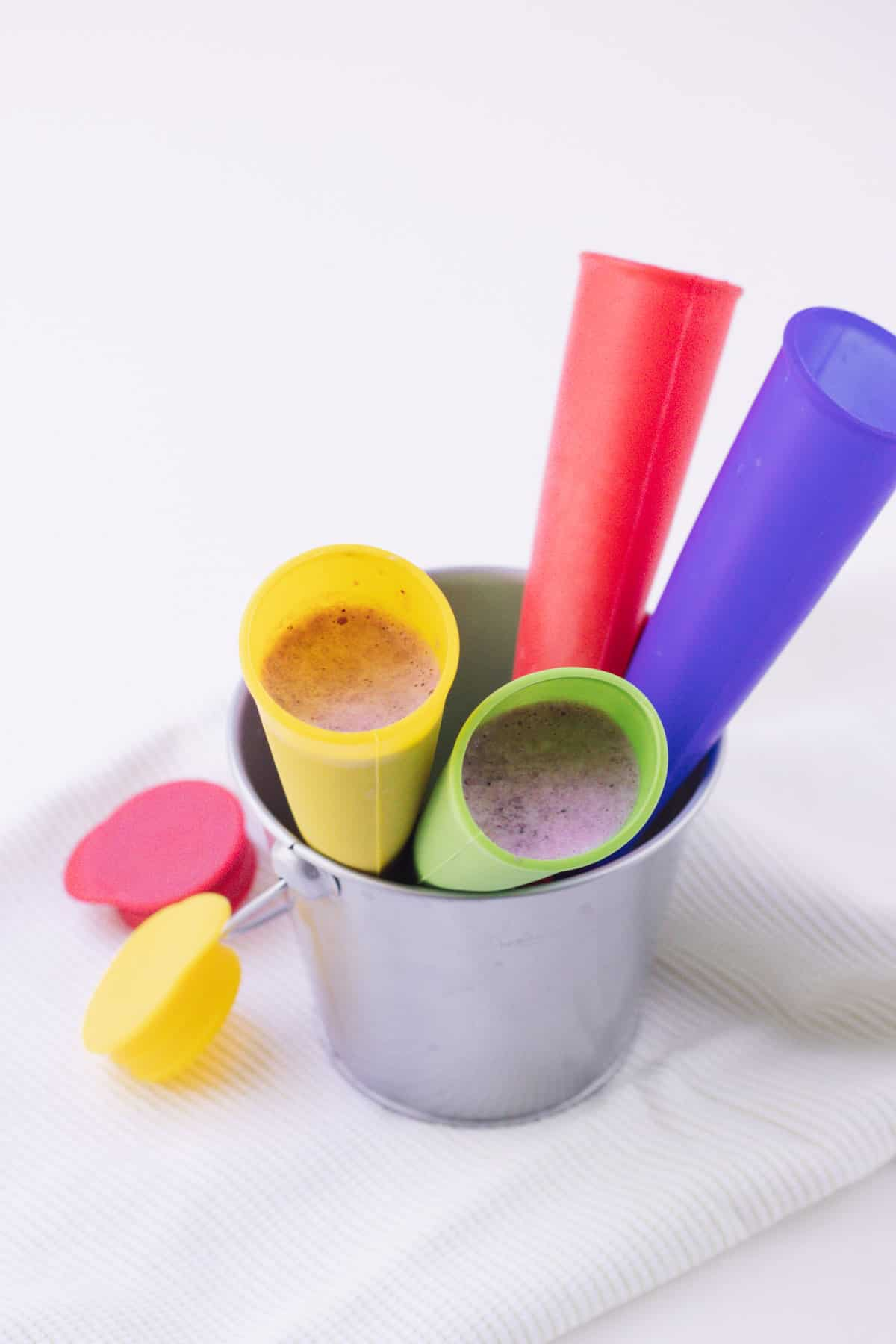 Multi-colored silicone freezer pop molds filled with PB&J smoothie in a small silver bucket and red and yellow lid to left.