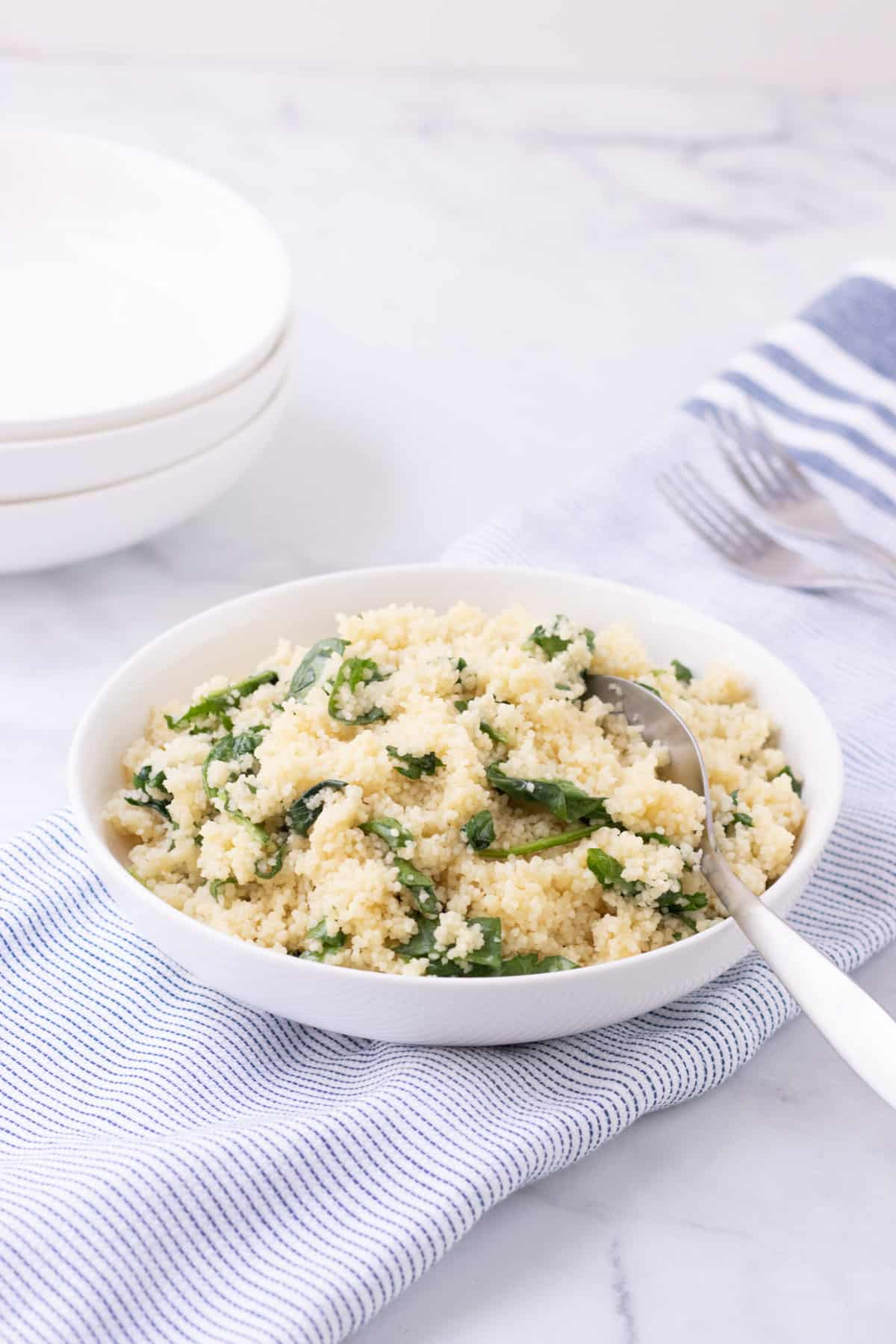White bowl  with spinach Parmesan couscous on blue and white striped linen with silver spoon and white bowls in left upper background.