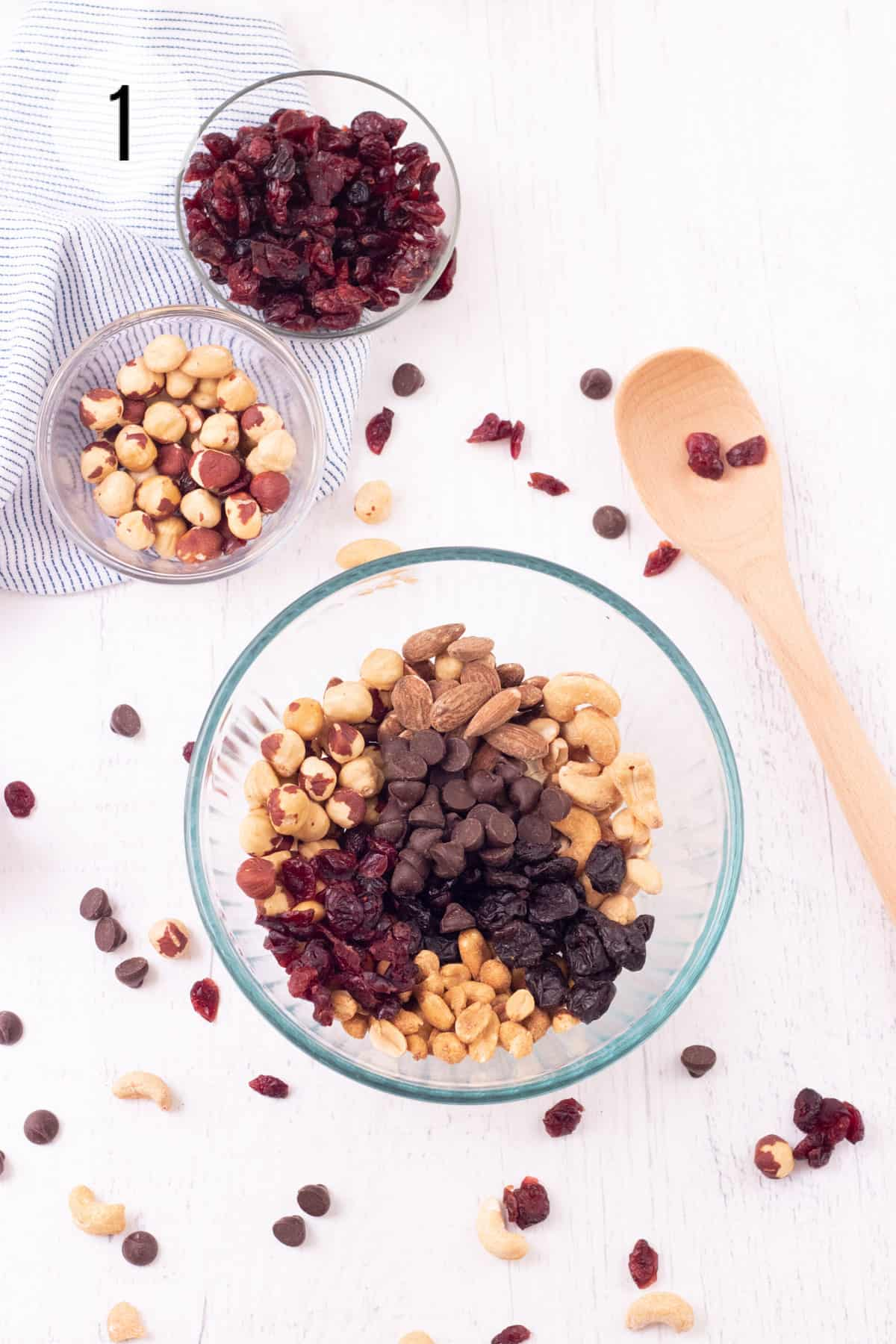 Glass bowl with roasted nuts, dried fruit and chocolate chips and sprinkle of ingredients on background with wooden spoon and smaller bowls of nuts in background.