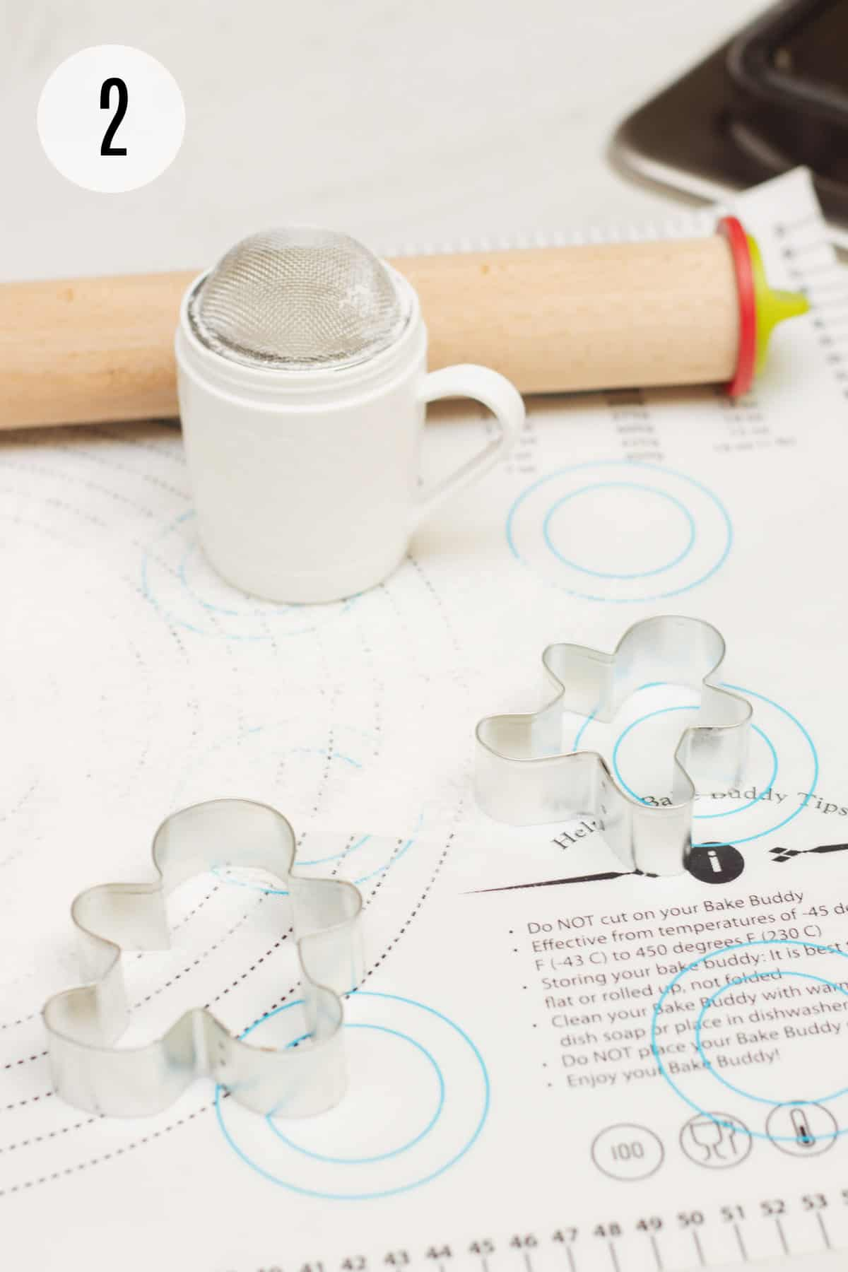 Printed baking mat with gingerbread man cookie cutters, powdered sugar/flour shaker and wooden rolling pin.