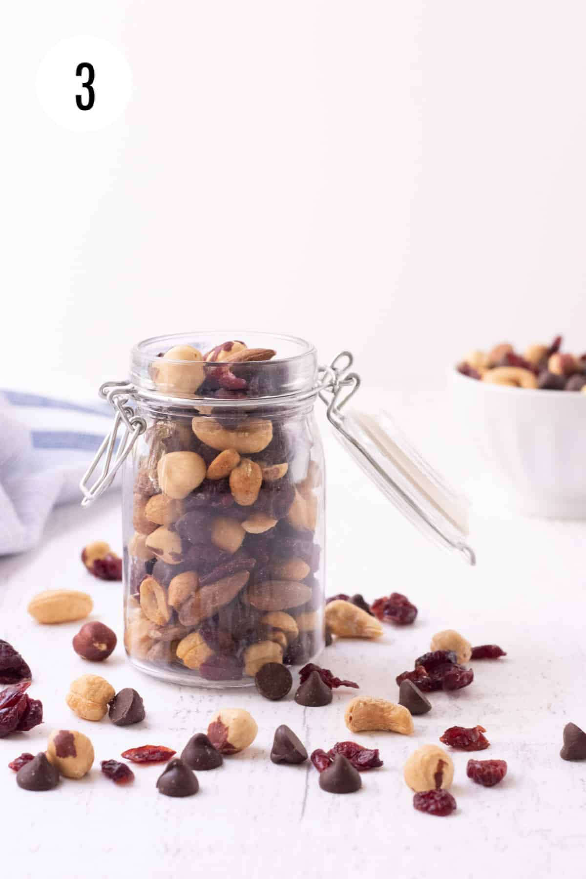 Glass jar with dark chocolate cherry trail mix and ingredients in foreground with white bowl of trail mix in background.