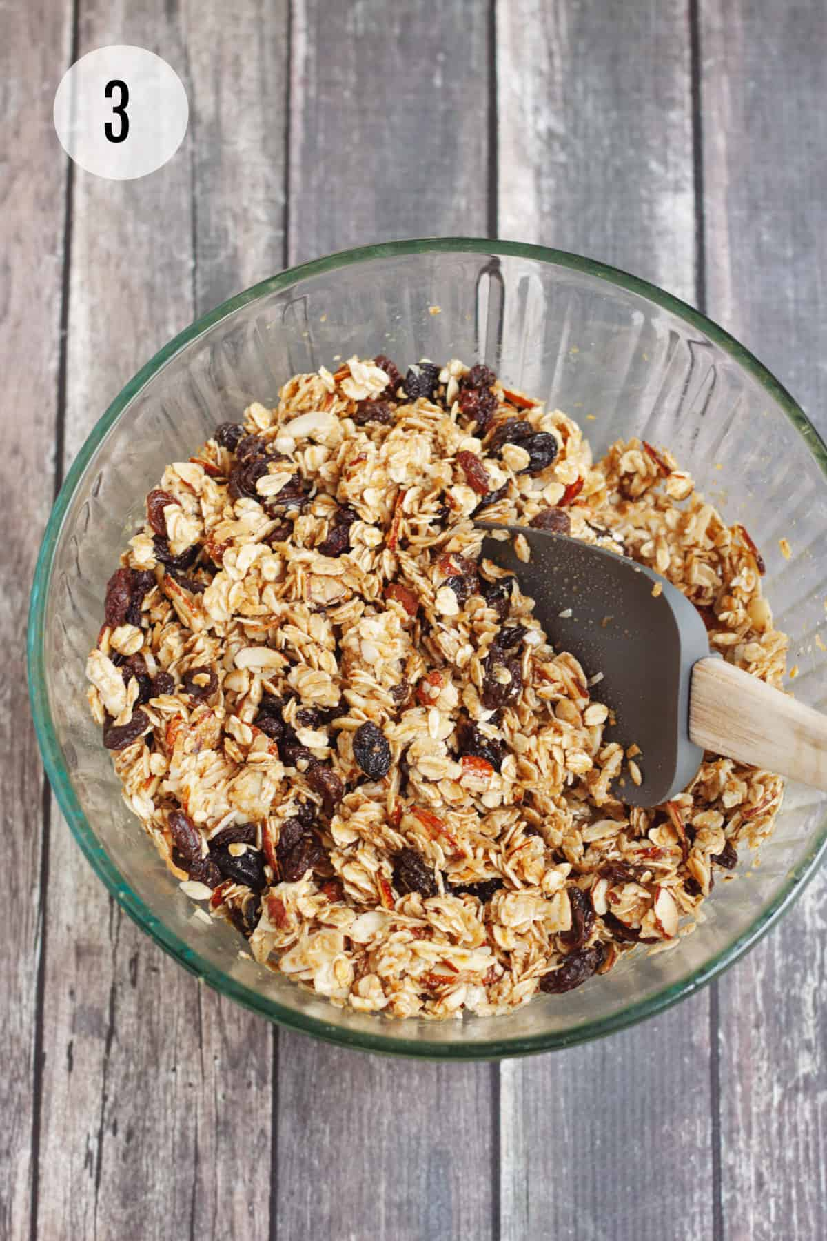 Glass bowl with homemade granola bar ingredients being stirred by grey rubber spatula.