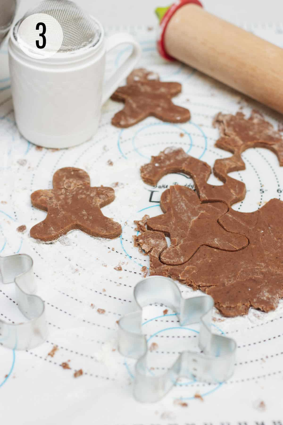 Mexican chocolate cut out sugar cookie dough on a baking mat cut into gingerbread man shape with flour/powdered sugar sifter and wooden rolling pin in upper background and metal cookie cutter in foreground.