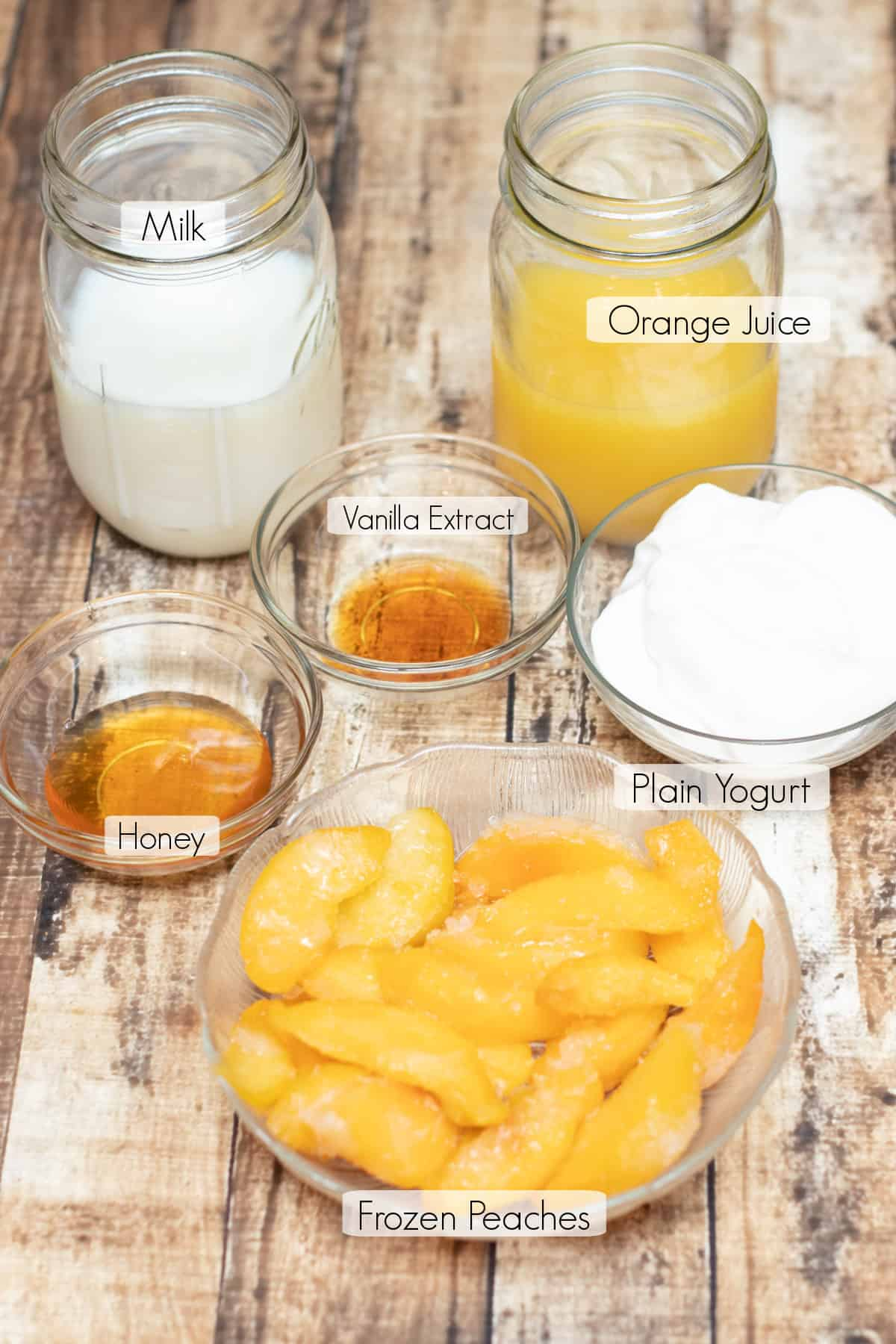 Labeled ingredients for making an orange peach smoothie.