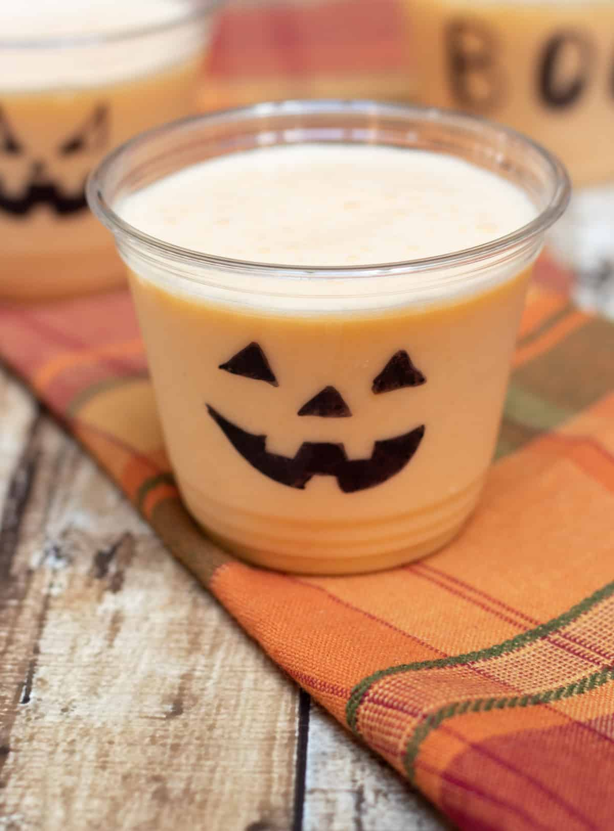Clear cup decorated with jack-o-lantern face with orange peach smoothie on an orange plaid napkin.
