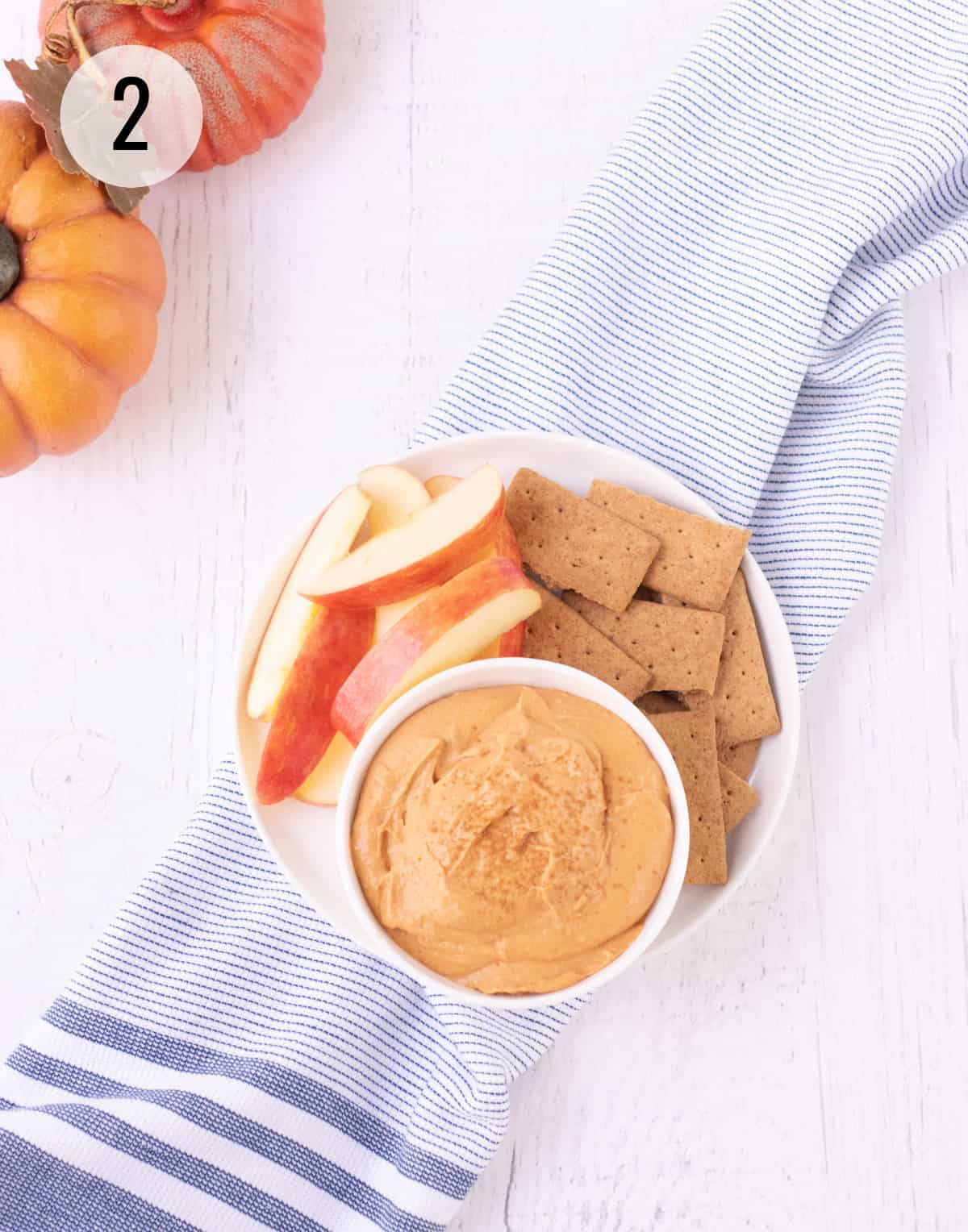 Top view of a bowl of pumpkin cheesecake dip sprinkled with ground cinnamon on a plate with apple slices and graham crackers on a blue and white striped towel with pumpkins in upper left corner.