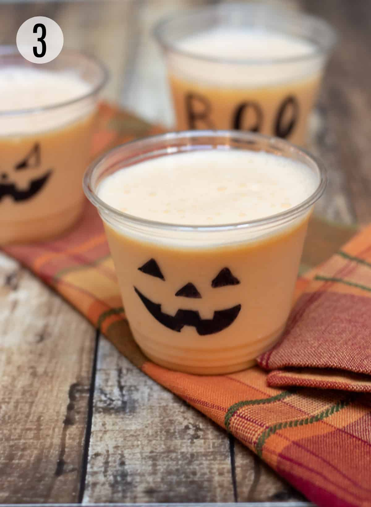 Clear cups decorated with jack-o-lantern faces and Halloween sayings filled with orange peach smoothie on an orange plaid napkin.