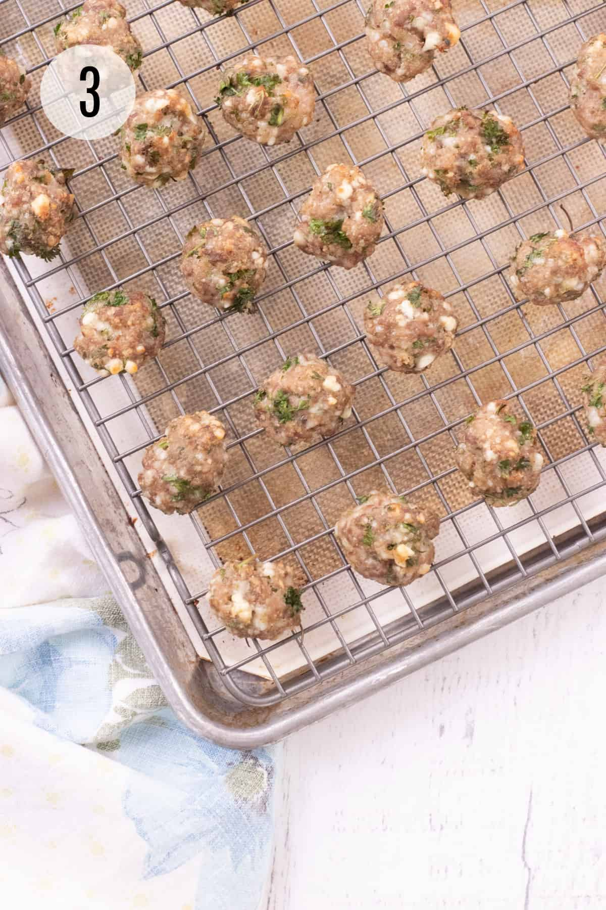 Metal baking rack with tan silicone baking mat on a baking sheet and cooked meatballs with parsley and cheese on baking rack.