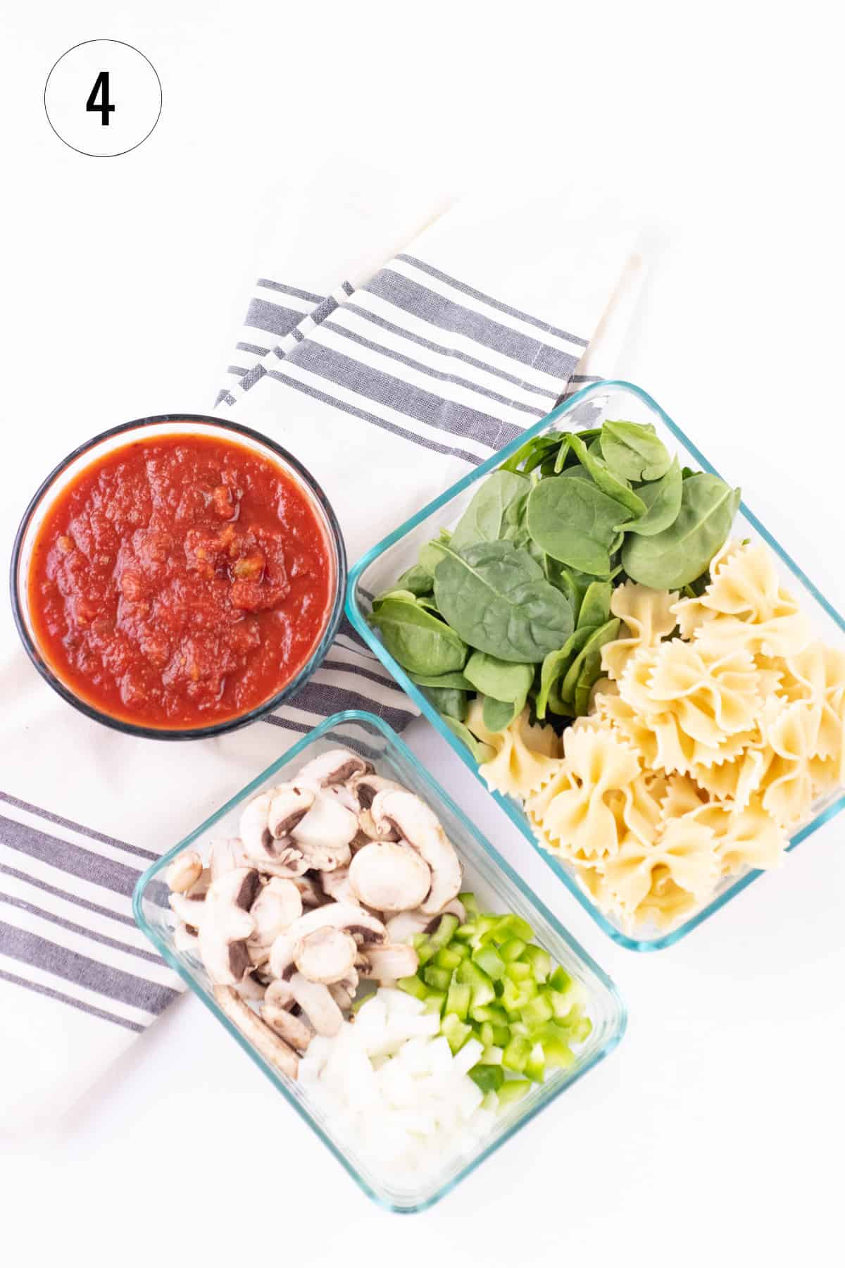 Glass containers filled with (clockwise from left) marinara sauce, baby spinach, cooked bow-tie pasta, diced green bell peppers and onions and sliced mushrooms on a striped towel to make stovetop lasagna.