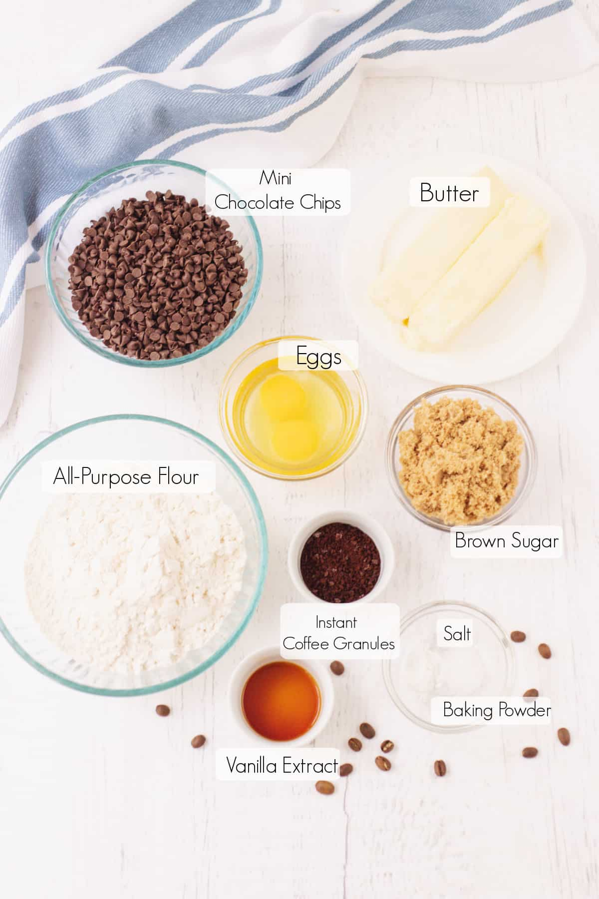 Labeled ingredients to make chocolate chip coffee cookies with blue and white towel in upper background.