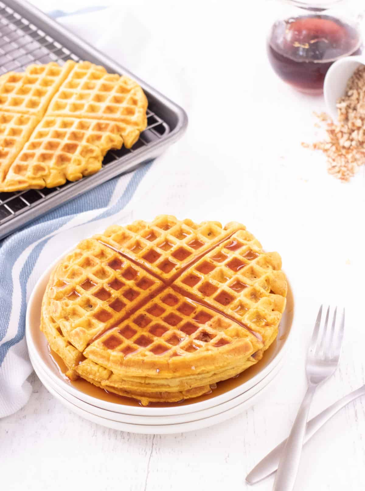 White plate of stacked pumpkin waffles with maple syrup on top and forks to side with baking sheet and rack of extra waffles and syrup and chopped nuts in upper backgrounds.