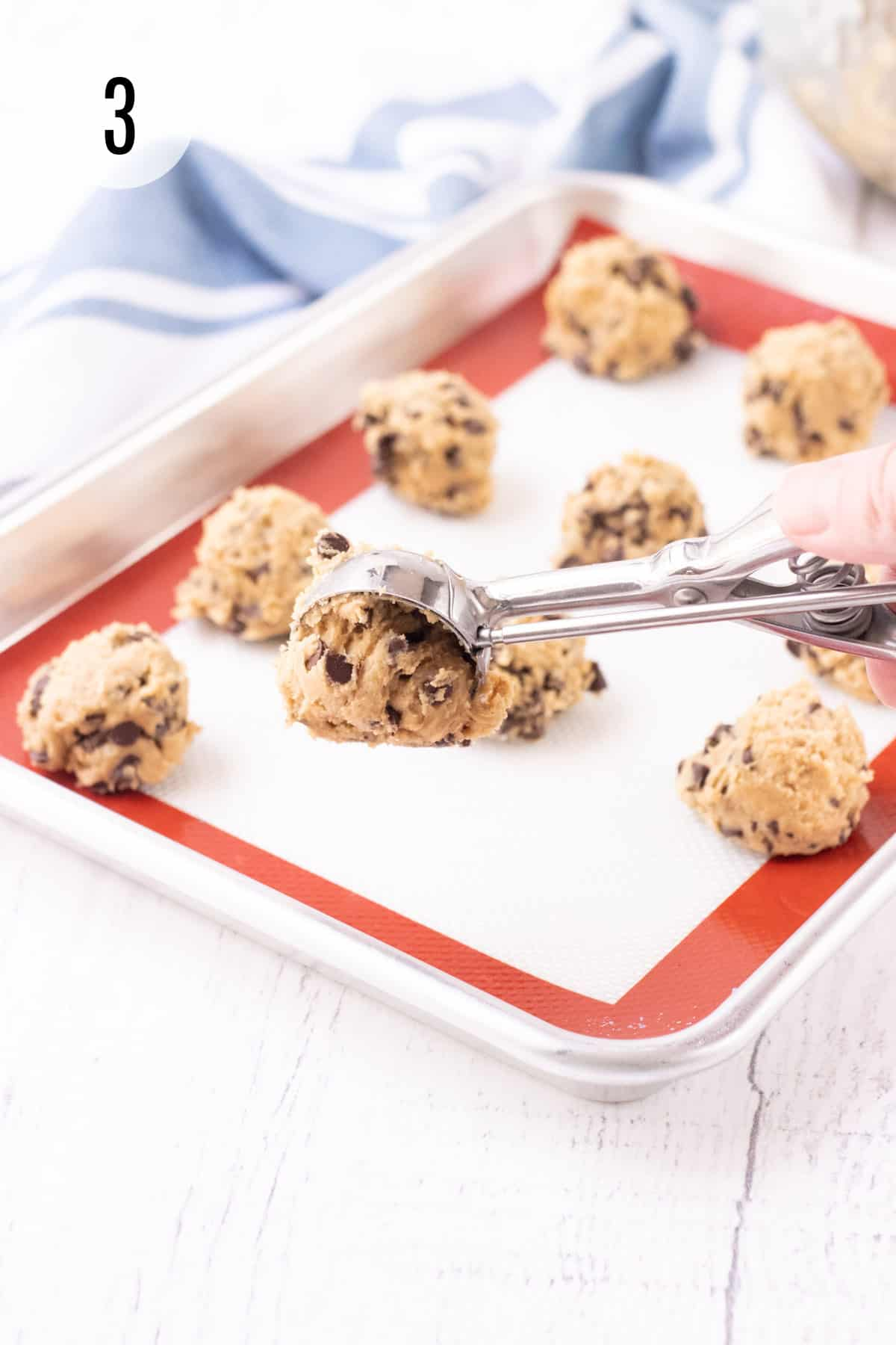 Cookie dough balls on a baking sheet lined with red and white silicone baking mat with silver scoop for dough with blue and white towel in background.