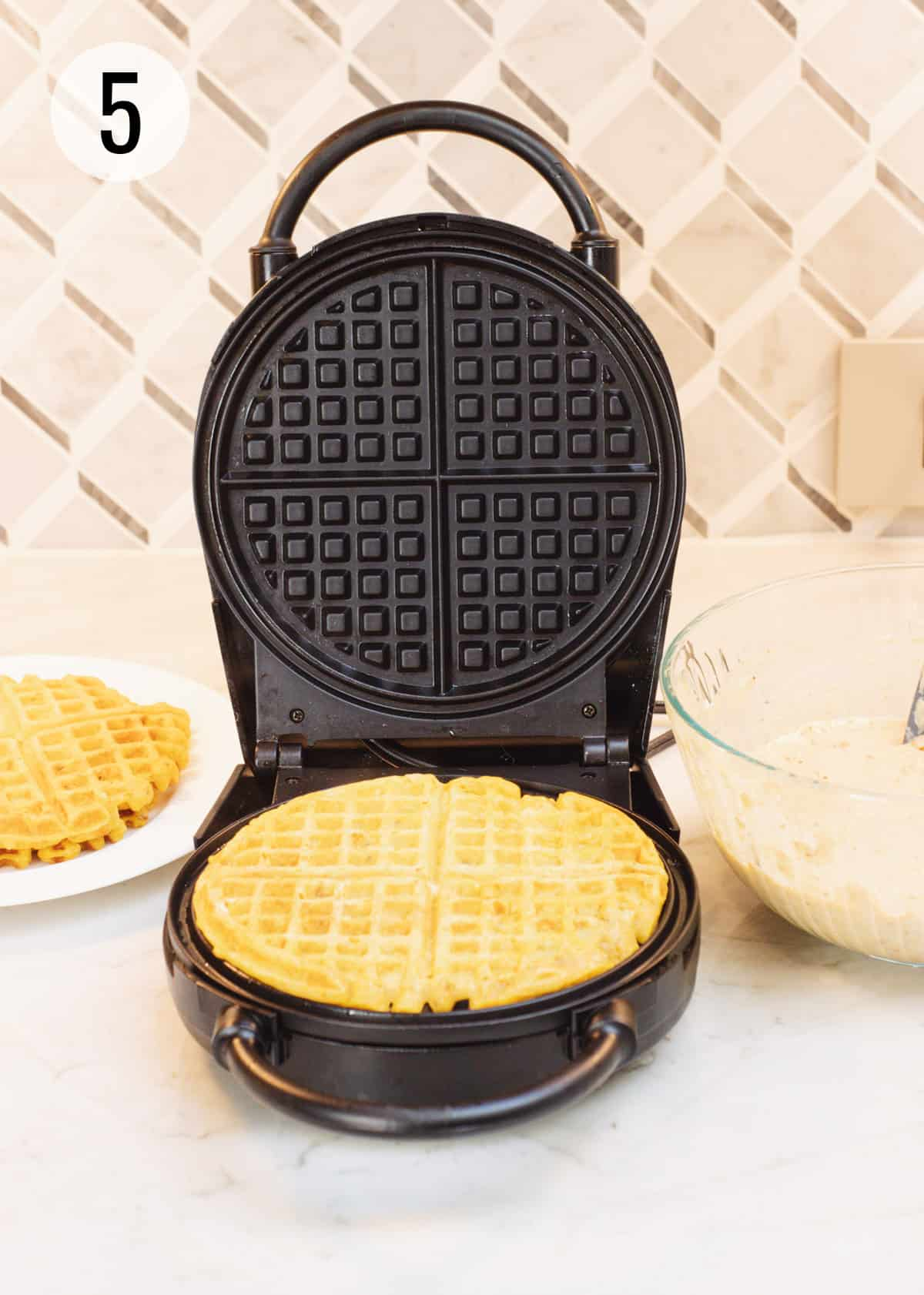 Round black waffle maker with baked pumpkin waffle on it and batter bowl to right and more baked waffles on a plate on left.