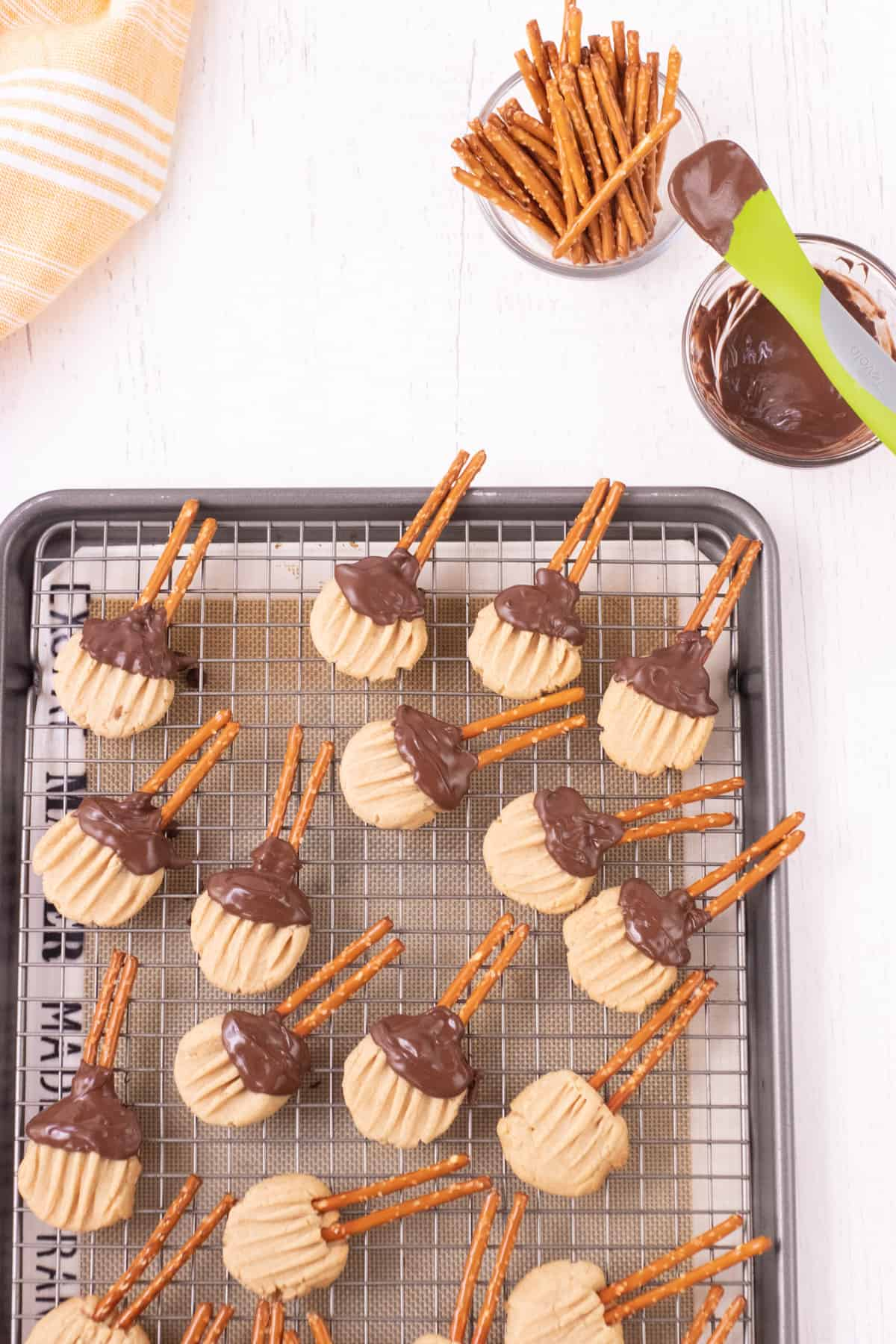 Brown sugar shortbread cookies with pretzels and melted chocolate shaped like witches brooms all on a baking rack with melted chocolate and pretzels sticks and orange towel in upper backgrounds.