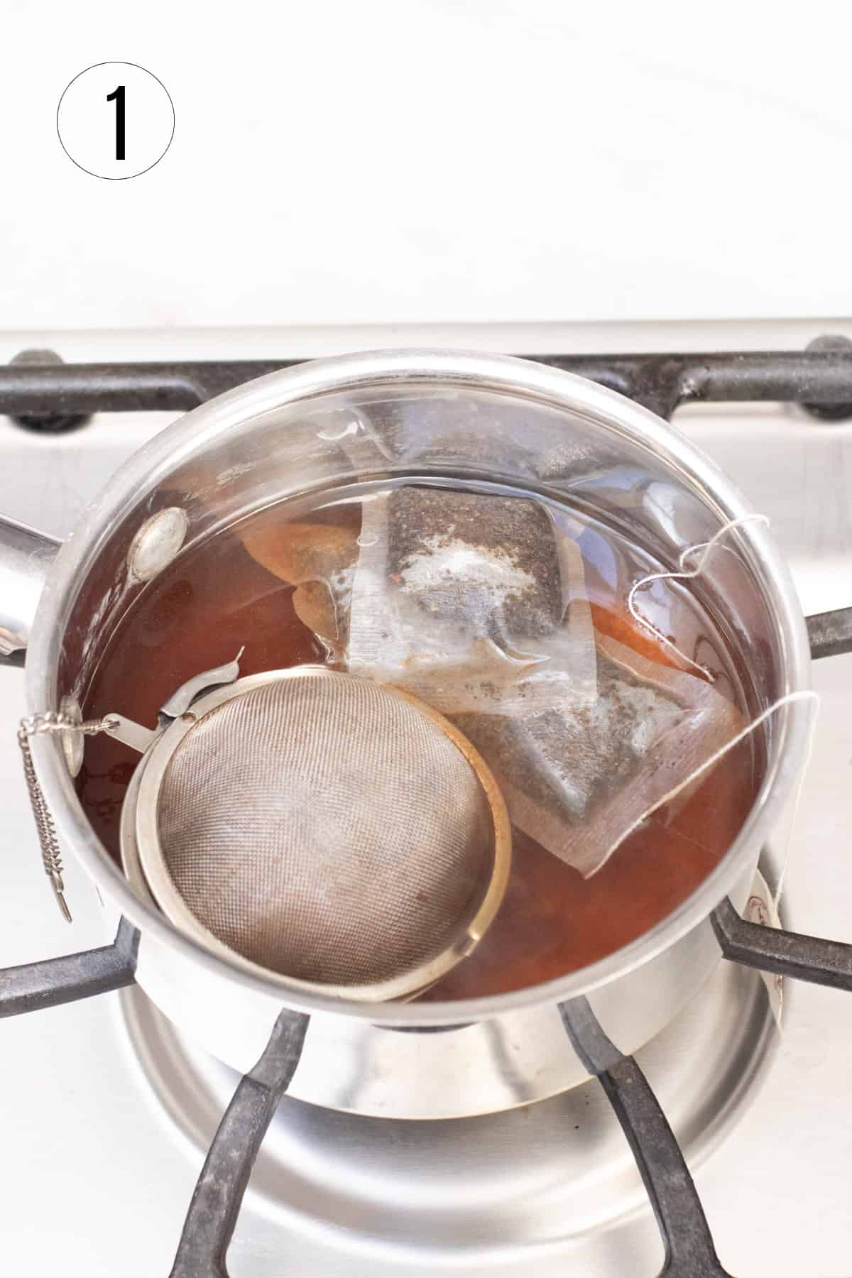 Silver saucepan with tea bags and spice ball steeping over hot stove.