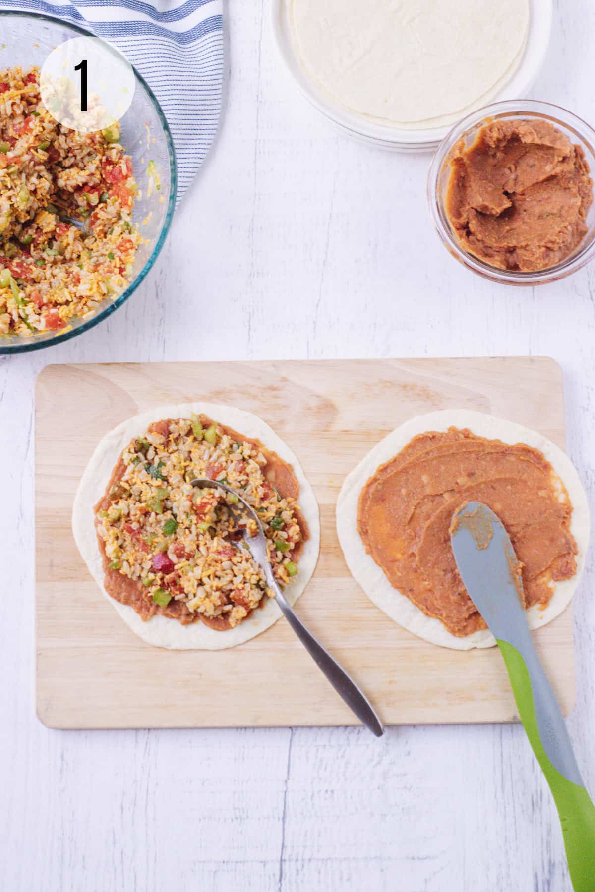 Wooden cutting board with flour tortillas spread using spoon and green and grey rubber spatula with vegetarian burrito filling and refried beans with bowls of each in upper background.