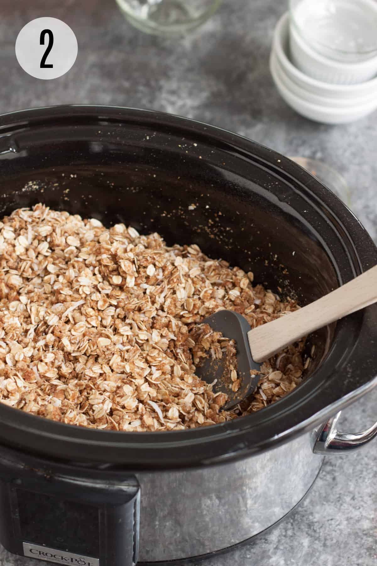 Black slow cooker with homemade granola mixture being stirred by grey rubber spatula with wooden handle and ingredient bowls in background.
