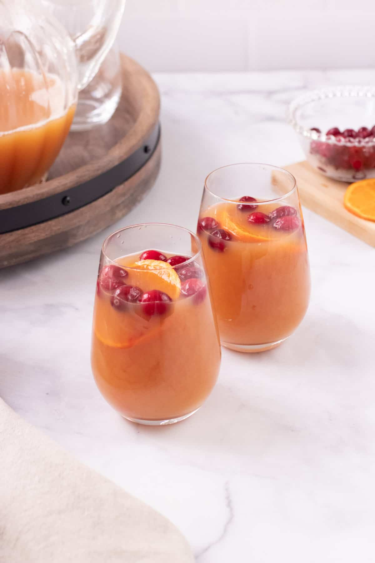 Two glasses of Orange Cranberry Tea with cranberries and orange slices floating as garnish and pitcher of tea mixture and bowl of cranberries and orange slices in background.