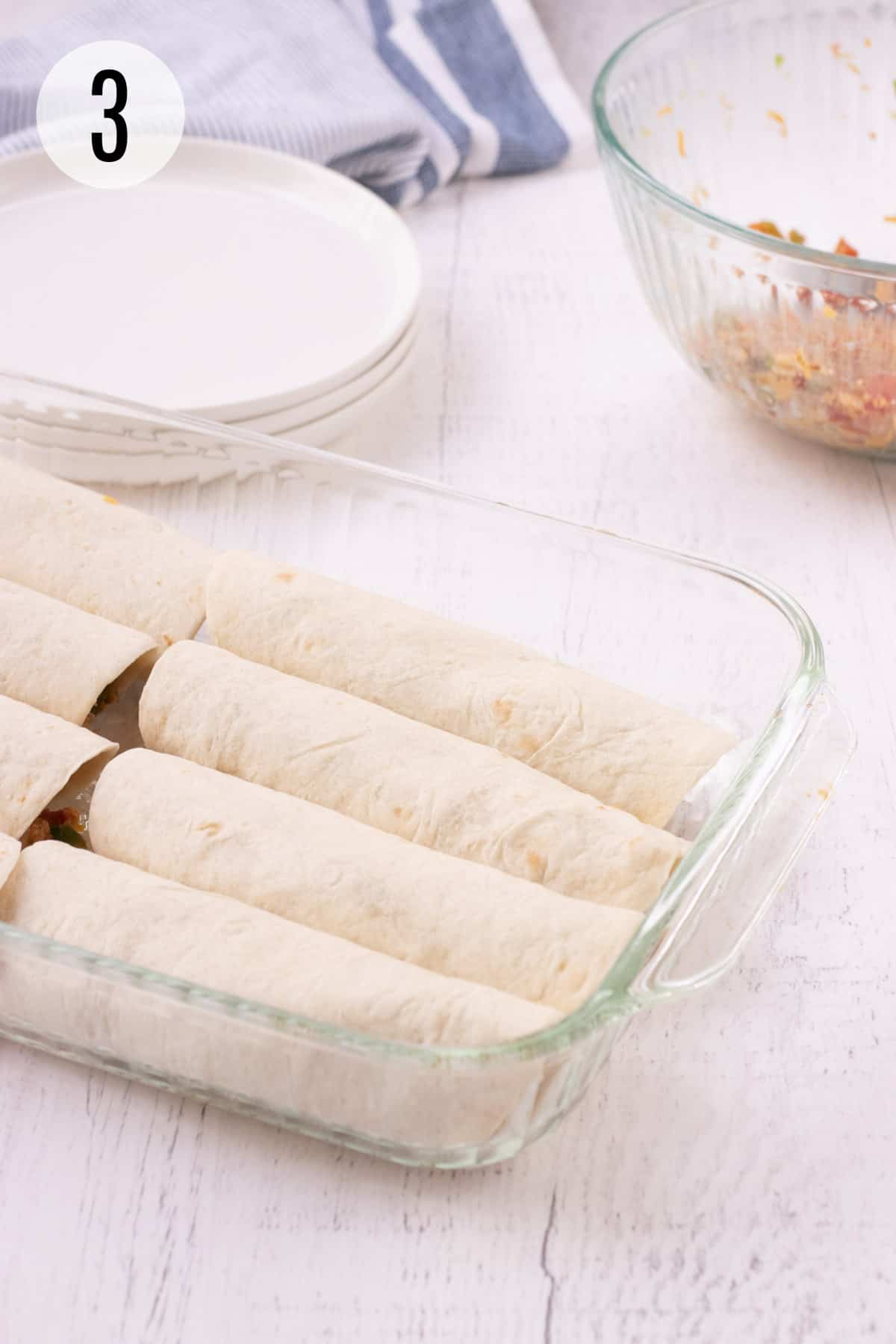Glass baking dish with rolled tortillas filled with burrito bite mixture and white plates, blue and white striped towel and glass bowl of mixture in upper background.