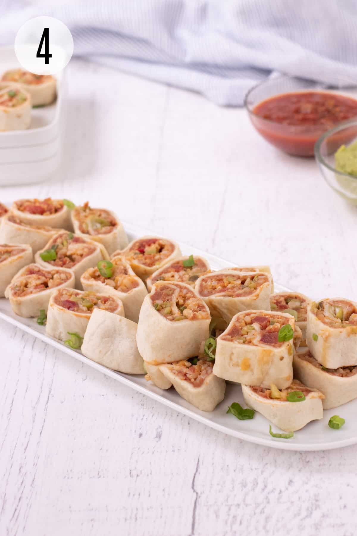 Platter with stacked burrito bites garnished with sliced green onions and plate of more bites and bowls of guacamole and salsa in upper background.