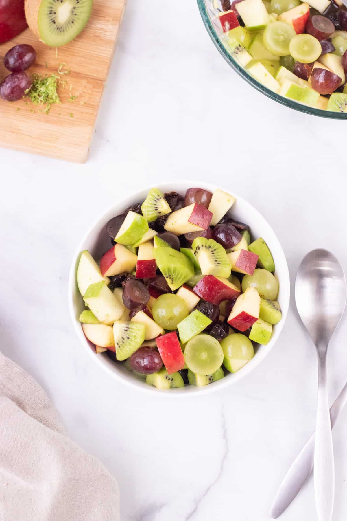 Top view image of holiday fruit salad in white bowl with red and green apples, red and green grapes, kiwi and dried cherries with wooden cutting board and glass bowl in upper right and left corners.