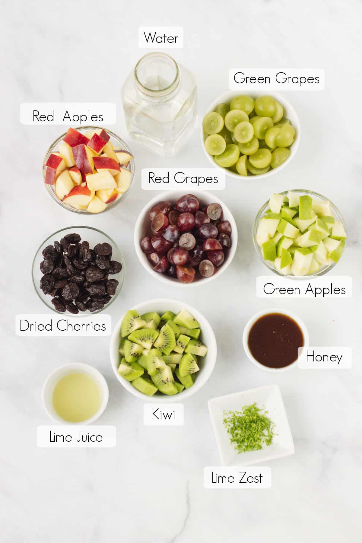 Labeled ingredients for Holiday Fruit Salad in bowls.