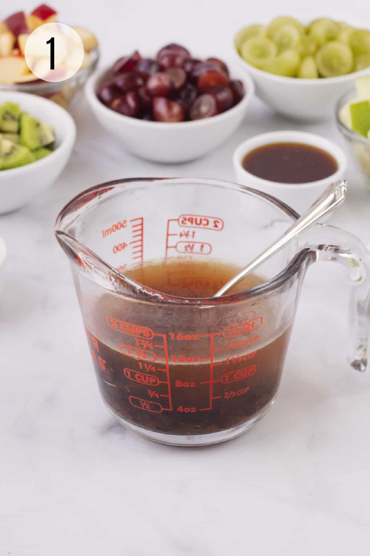 Glass measuring cup with water and dried cherries soaking and ingredients for Holiday Fruit Salad in bowls in background.