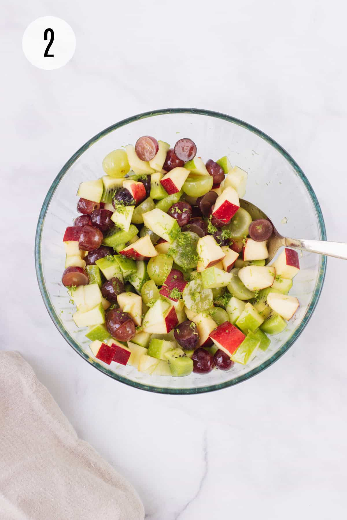 Top view image of Holiday Fruit Salad with chopped apples, grapes, kiwi and lime zest in a glass bowl being stirred by silver spoon.