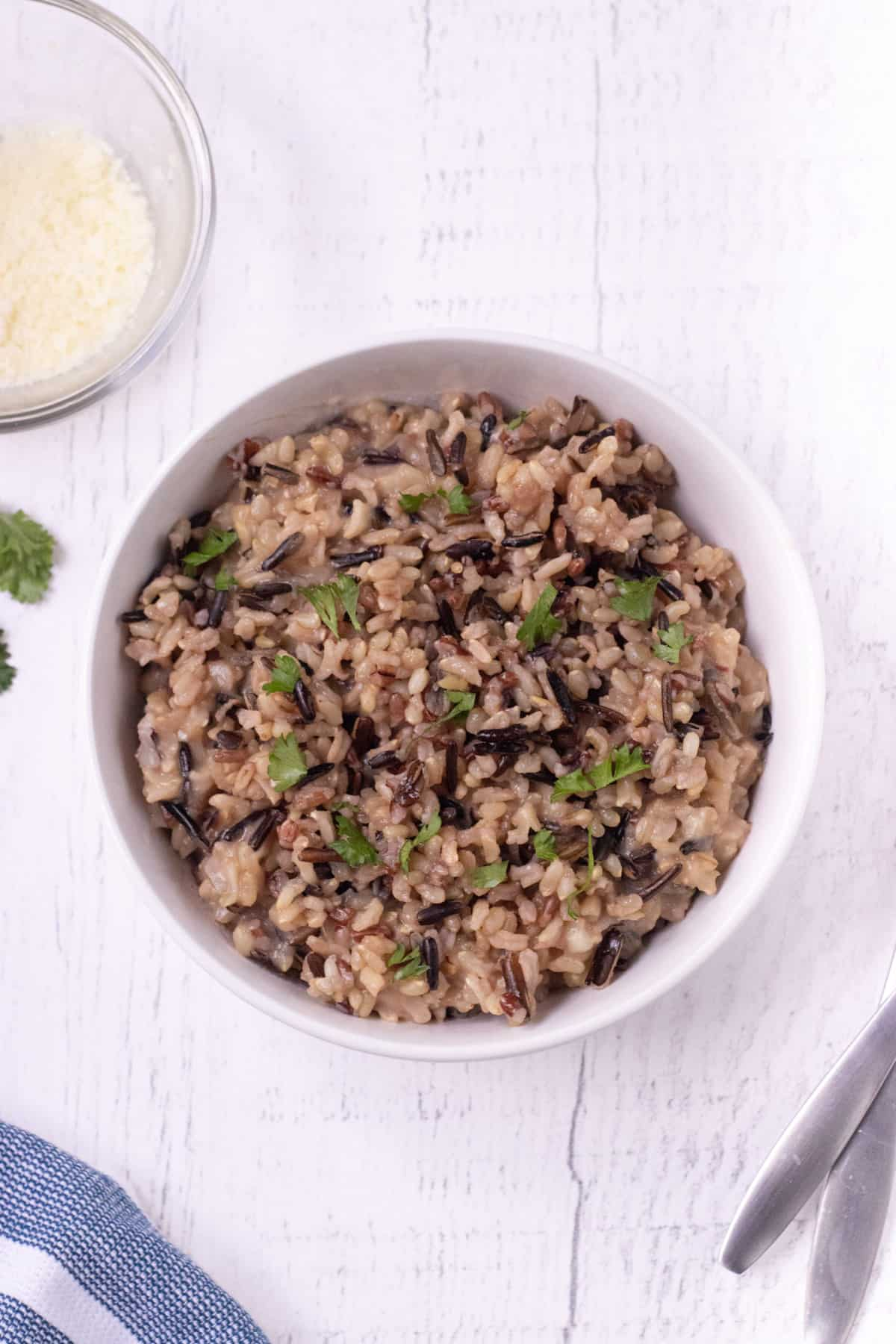 Top view of brown and wild rice in a white bowl with parsley for garnish and a bowl of grated parmesan cheese in upper left corner.