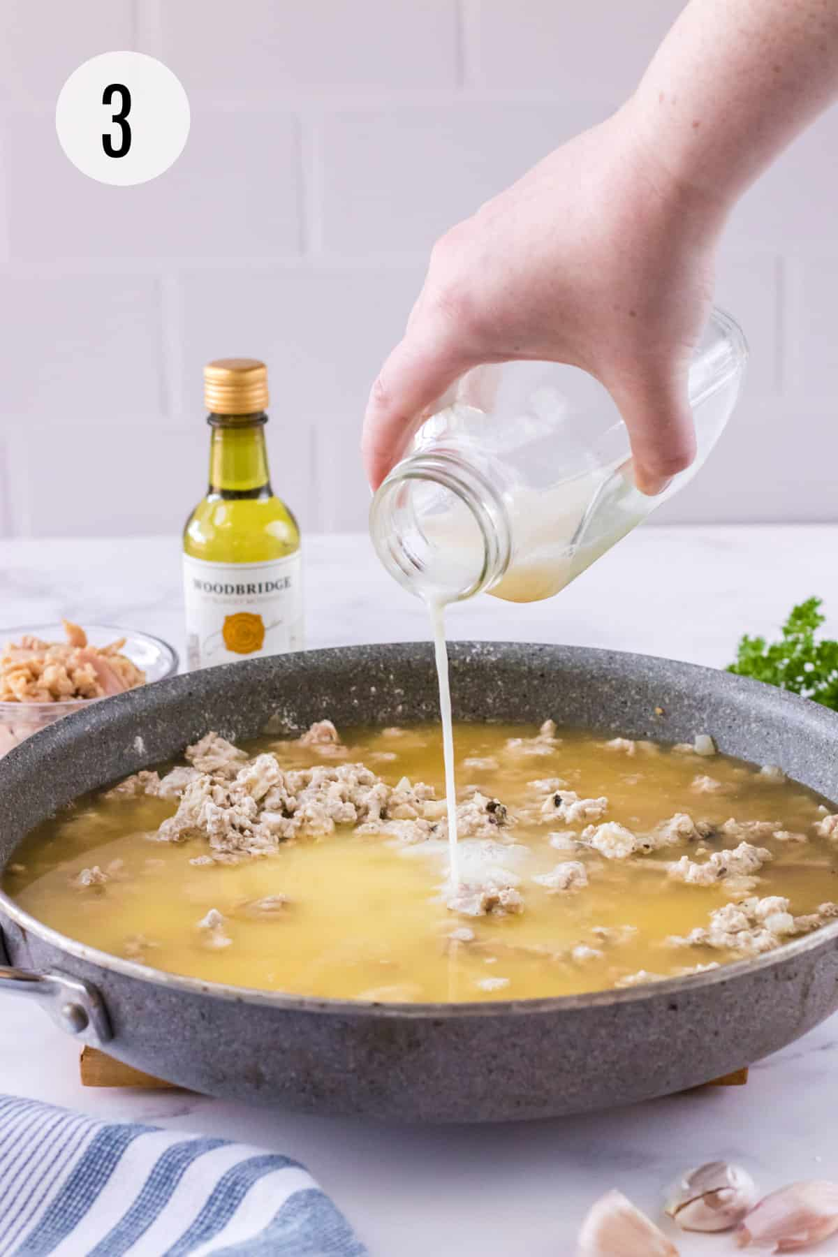 Grey skillet with ground turkey mixture and chicken broth and pouring milk into sauce with other ingredients surrounding.