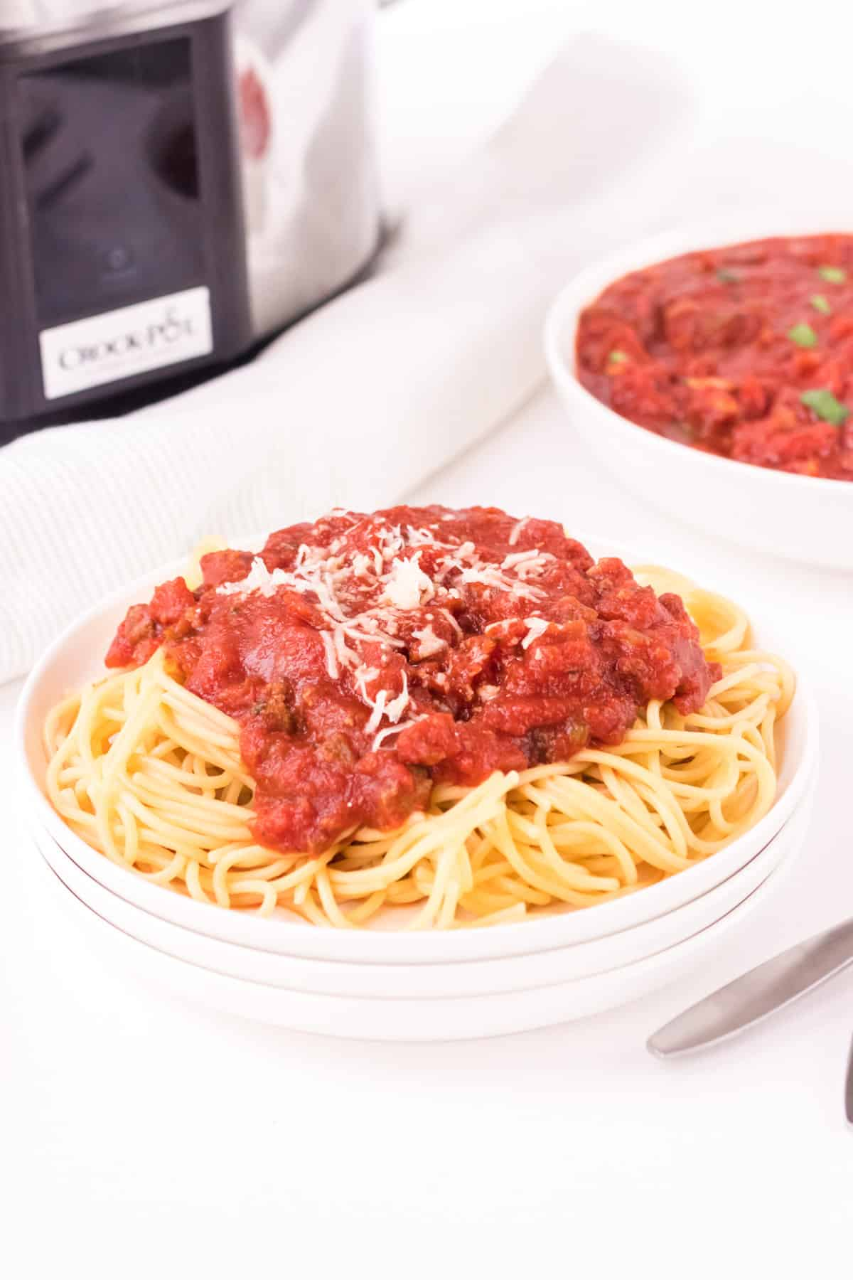 Stack of white plates with spaghetti and meat sauce topped with shredded cheese with bowl of sauce and slow  cooker in background.